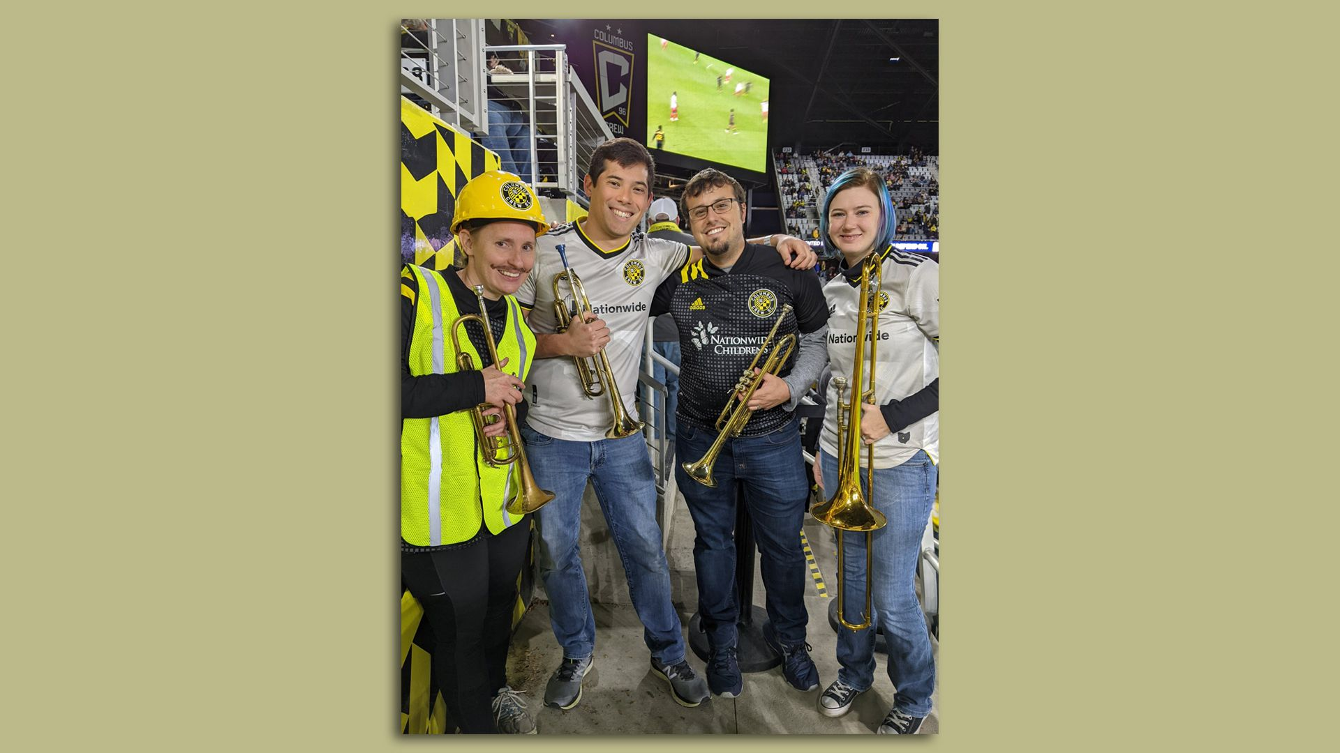 Four trumpet and trombone players pose at a soccer game, wearing the team's attire.