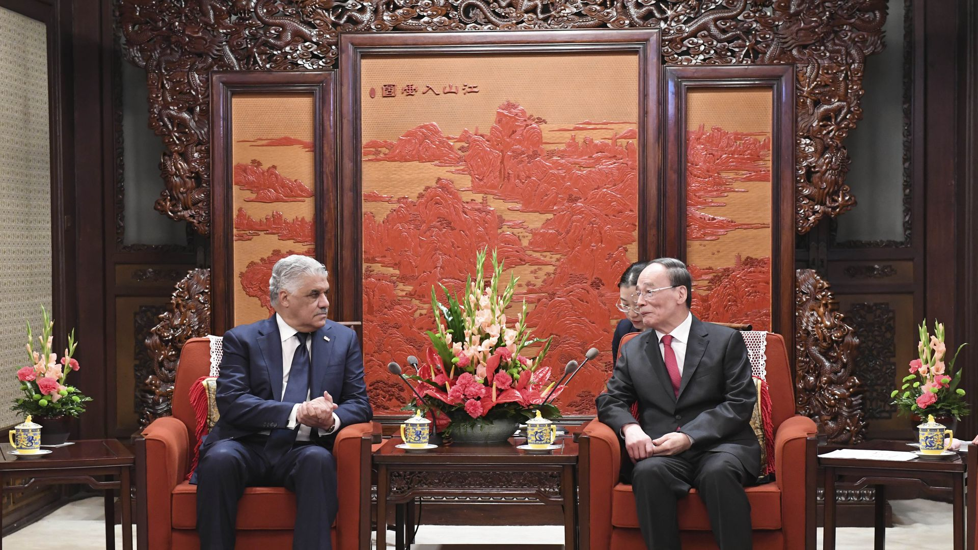 Dominican and Chinese leaders sit on armchairs in front of an orange and red painting