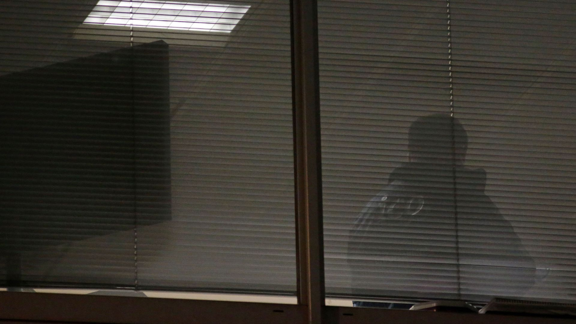 A man is seen through blinds inside the offices of Cambridge Analytica in central London.
