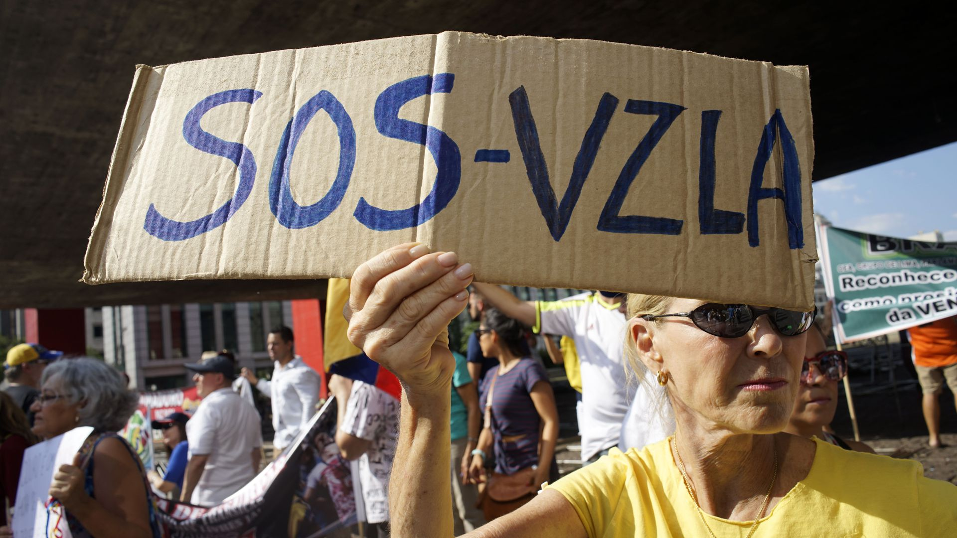 Woman holding SOS-Venezuela sign