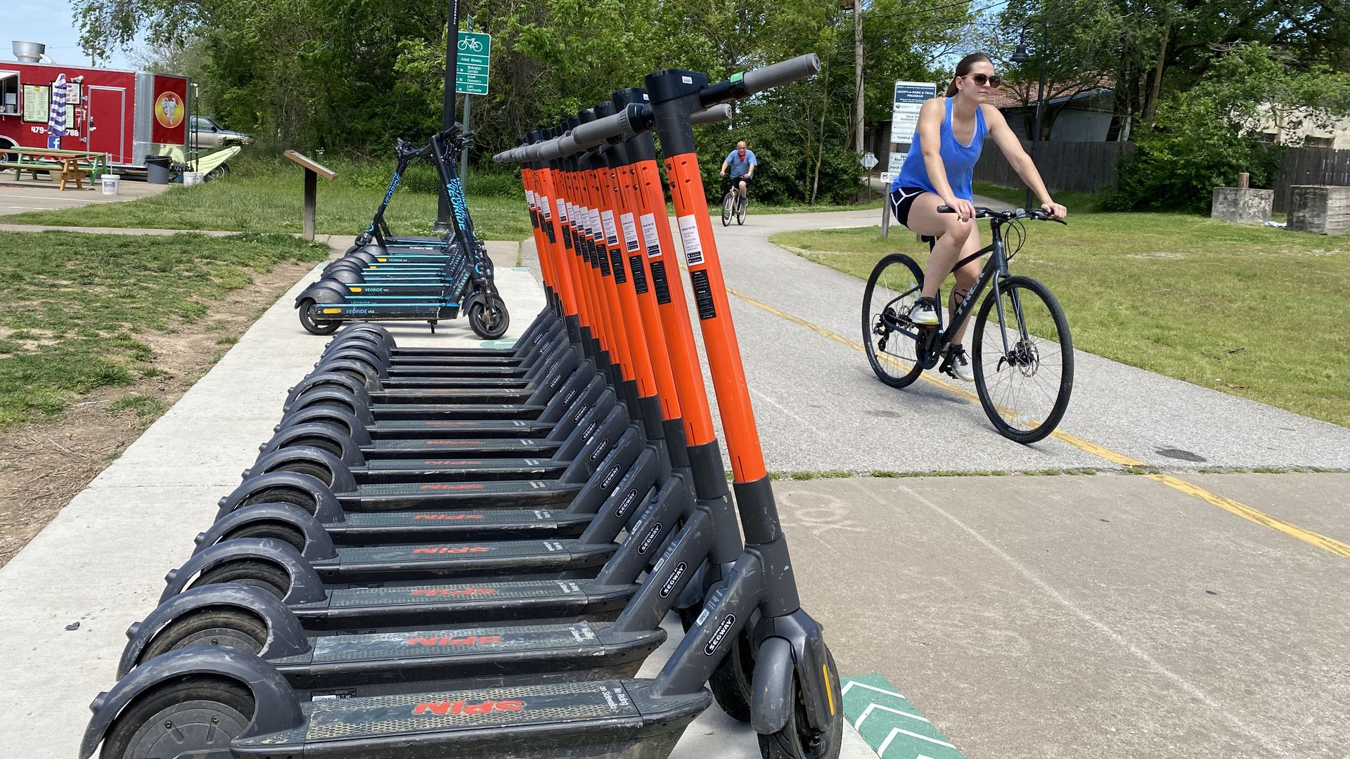 A woman rides a bike past a fleet of electric scooters