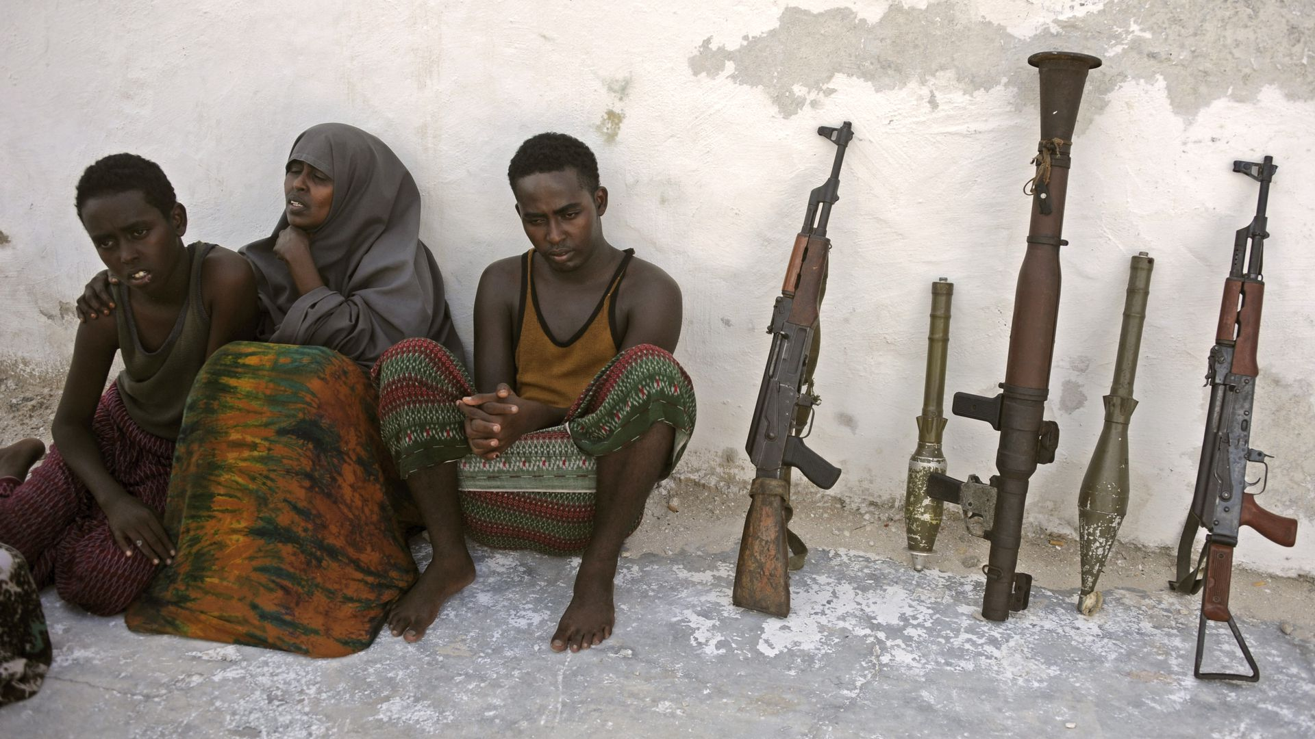Suspected Al Qaeda-aligned Shabaab militants, a woman and her three children, sit next to weapons after their arrest on May 5, 2016 in Mogadishu