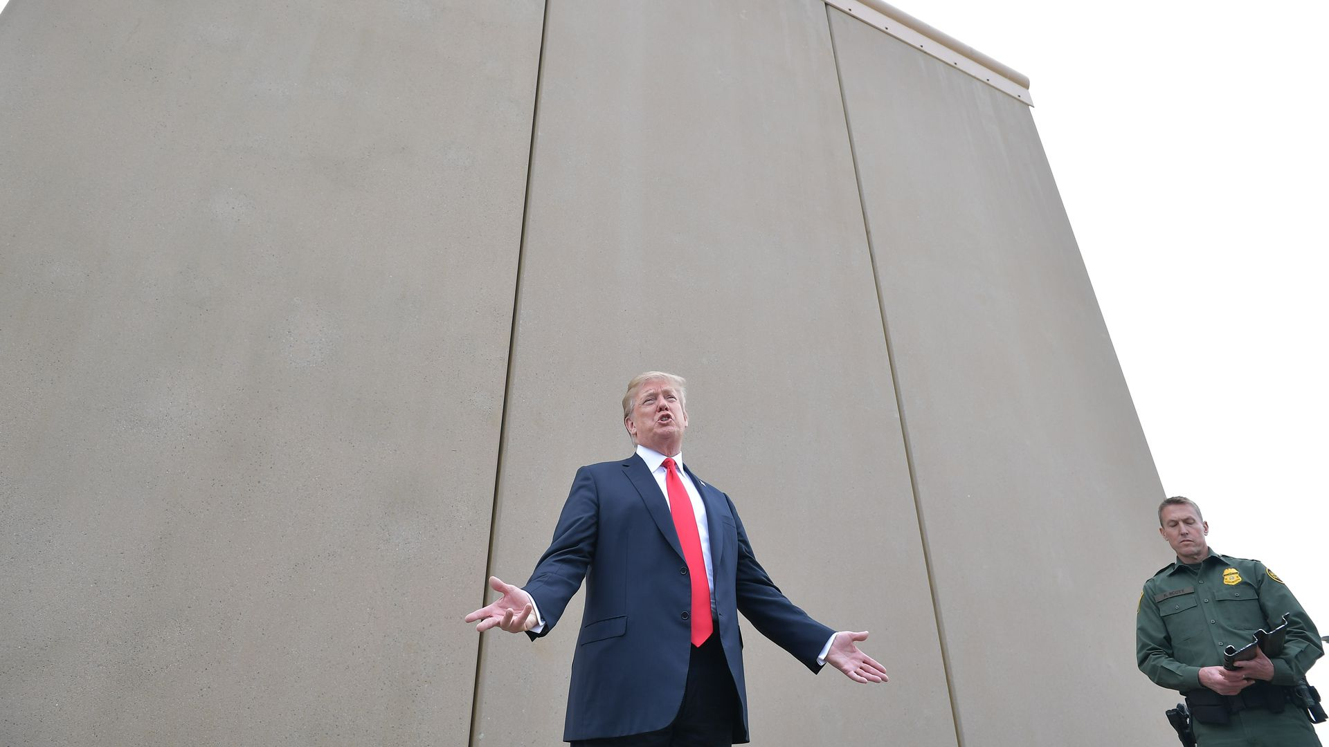 In this image, Trump stands in front of a border wall prototype.