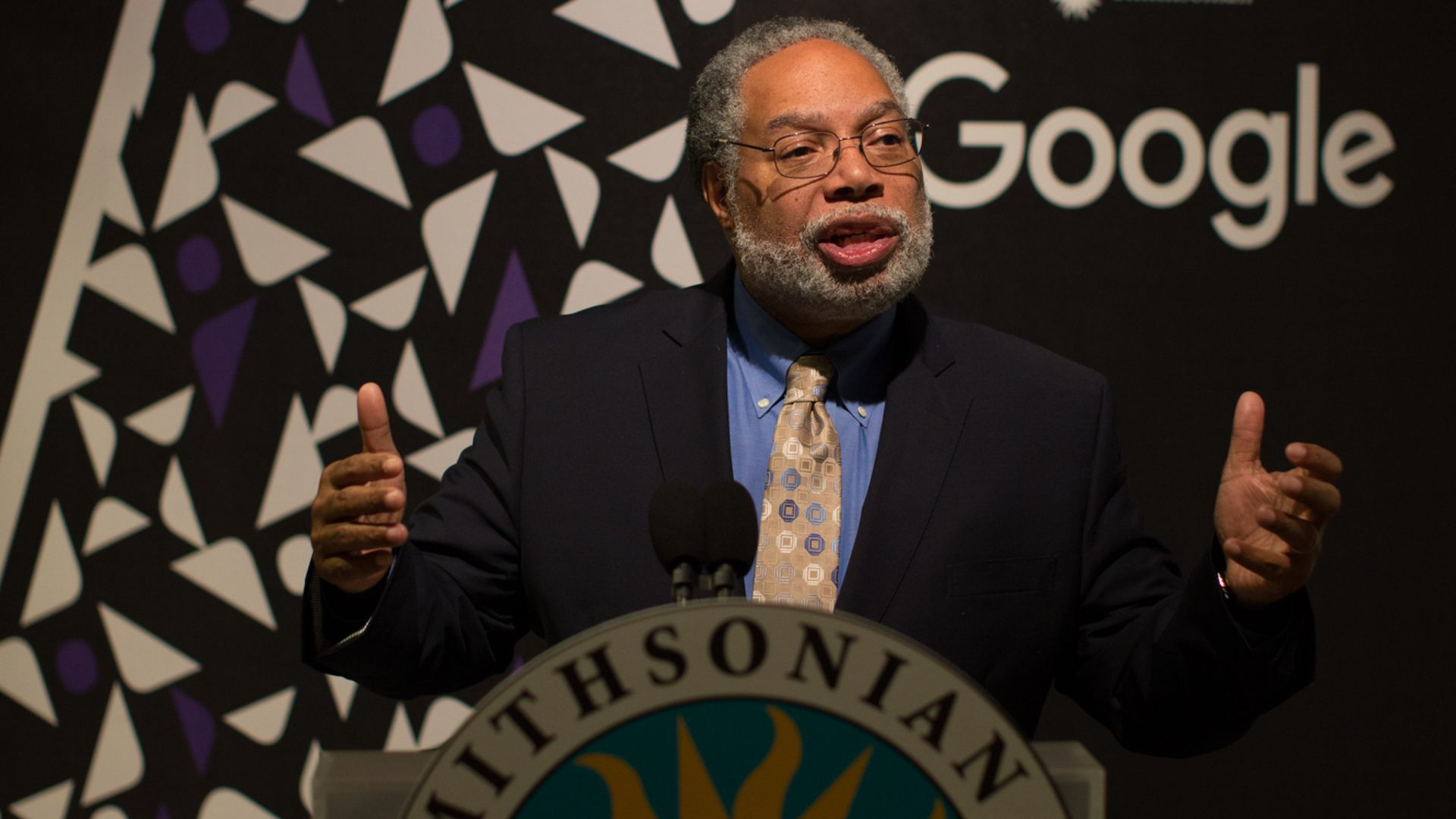 Lonny Bunch, founding director of the Smithsonian's National Museum of African American History and Culture, speaking at a podium