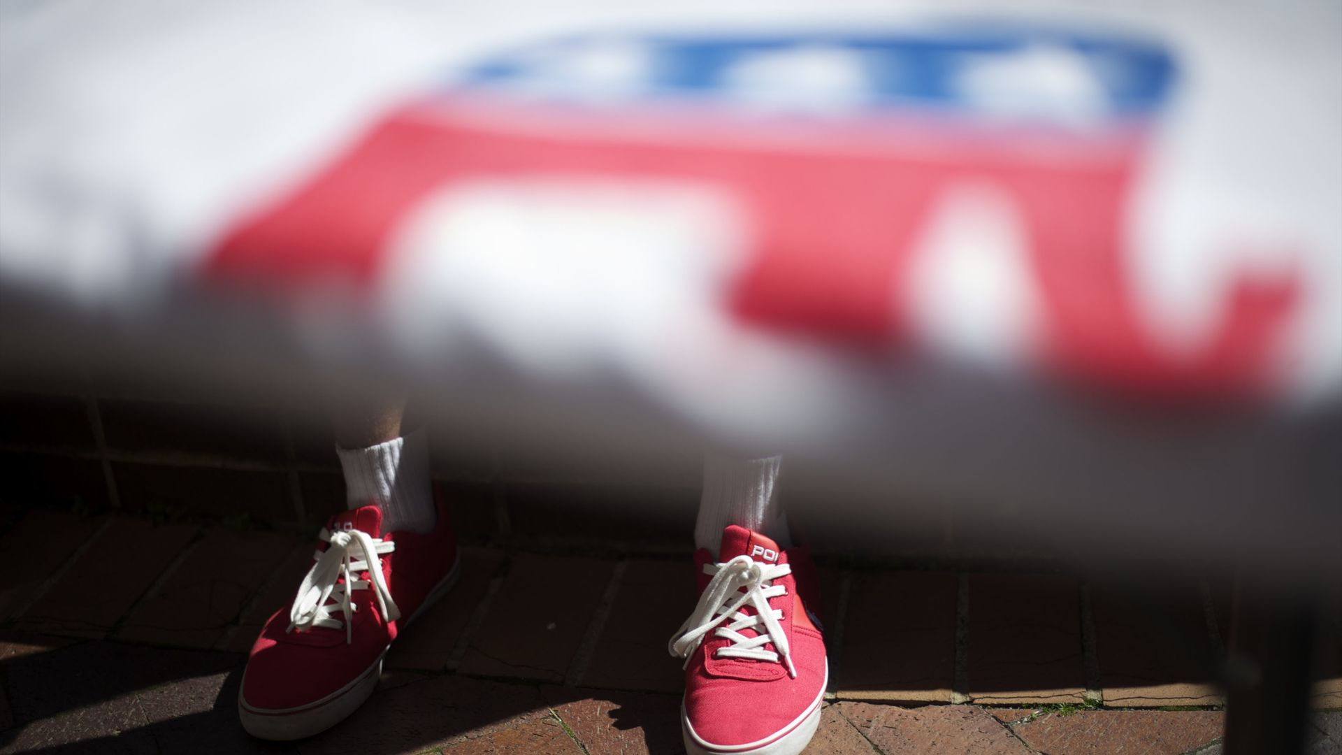 A boy with converse stands under a flag with the GOP elephant on it