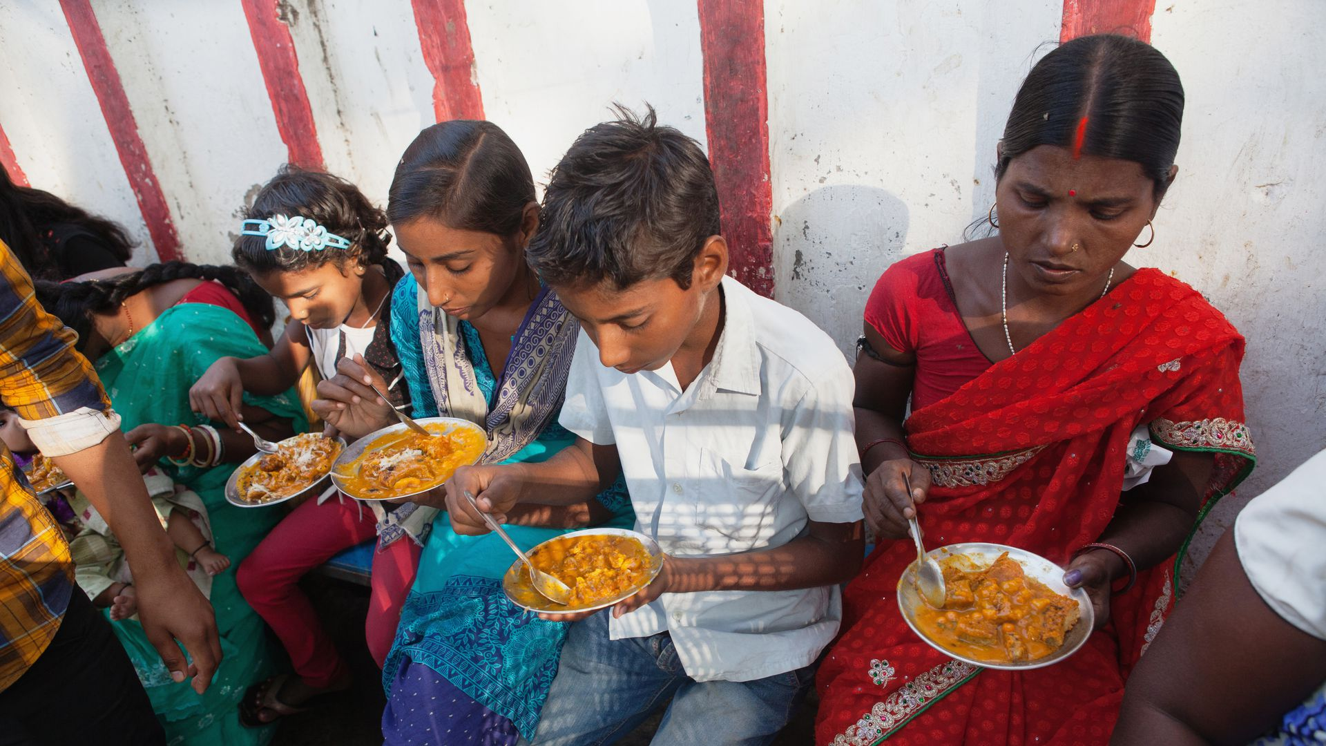 India, Bihar, Bodhgaya, A family eating vegetarian street food in Bodh.