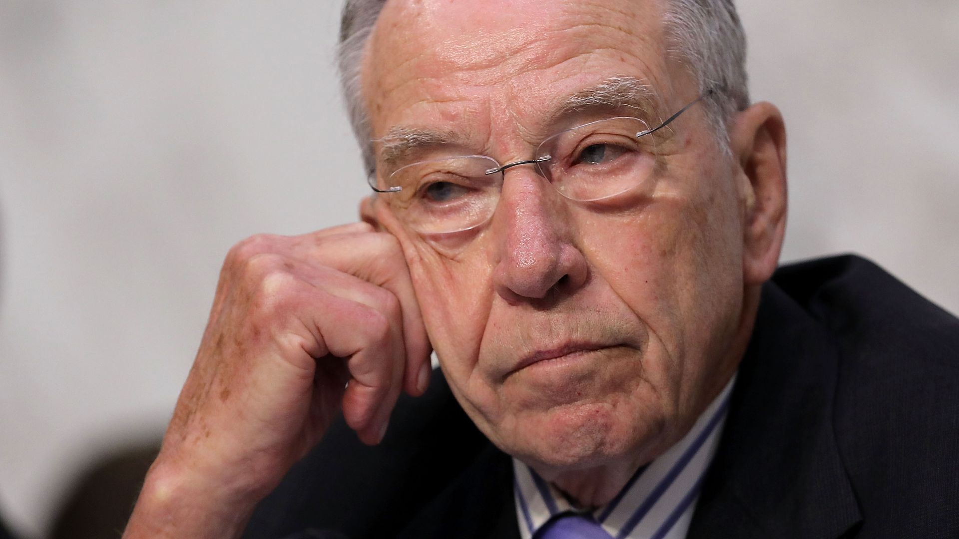 Chuck Grassley rests his head on his hand while in thought