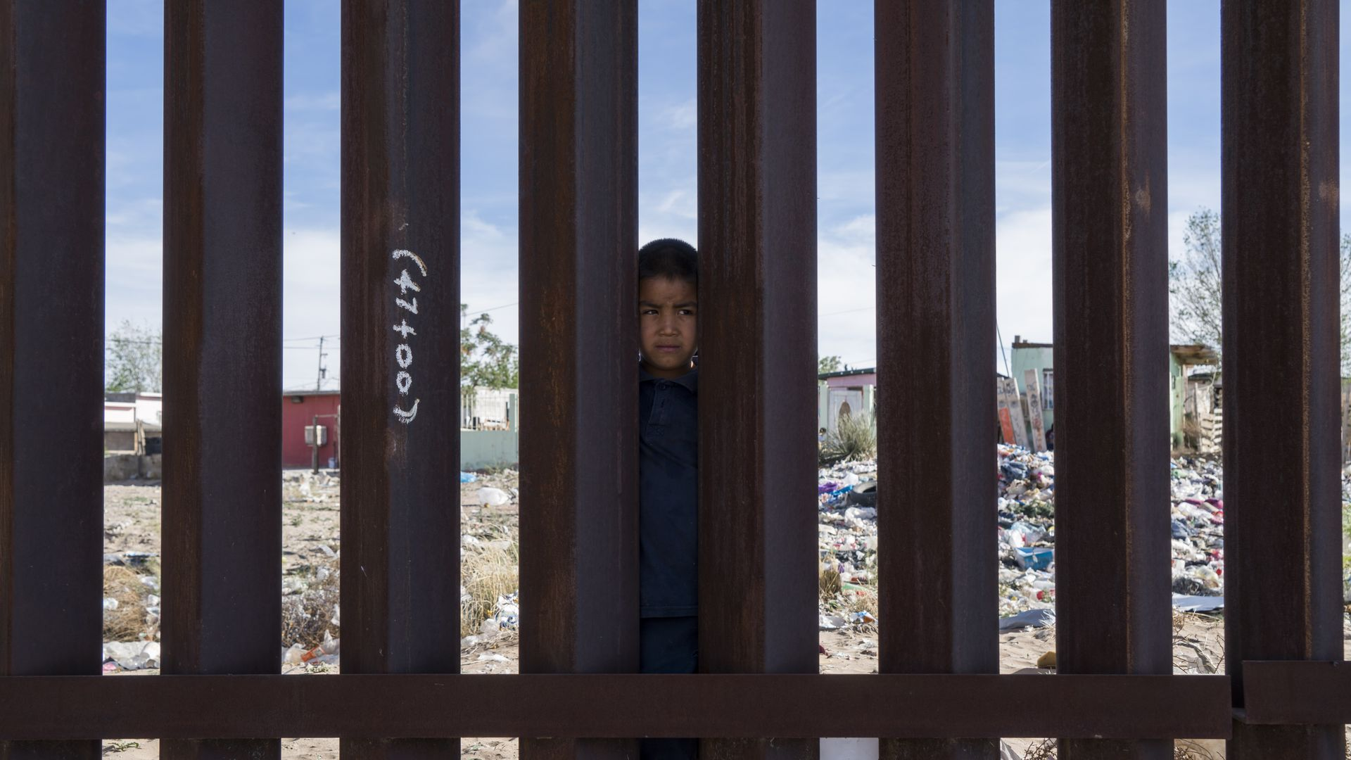 Little boy stand on the Mexico side of the border wall with his head peeking through the slats of the metal fence.