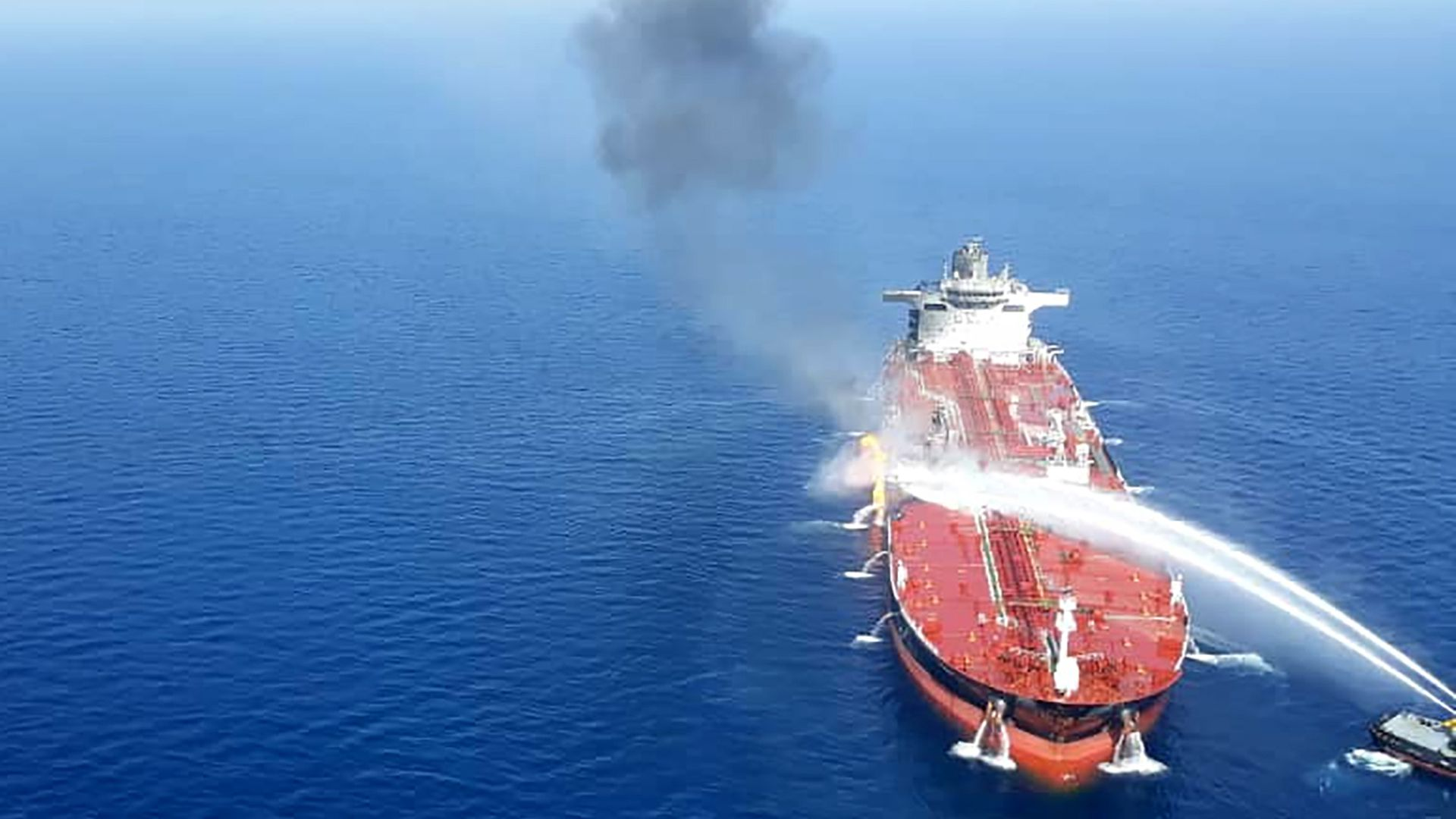 In this image, jets of water are shot onto a large oil tanker on the ocean.