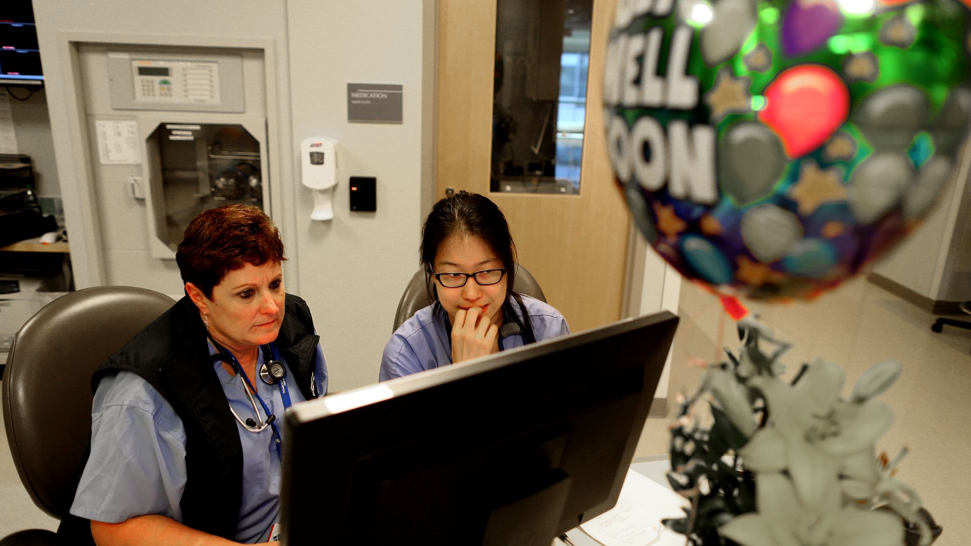 Two nurses look at a computer at a hospital.