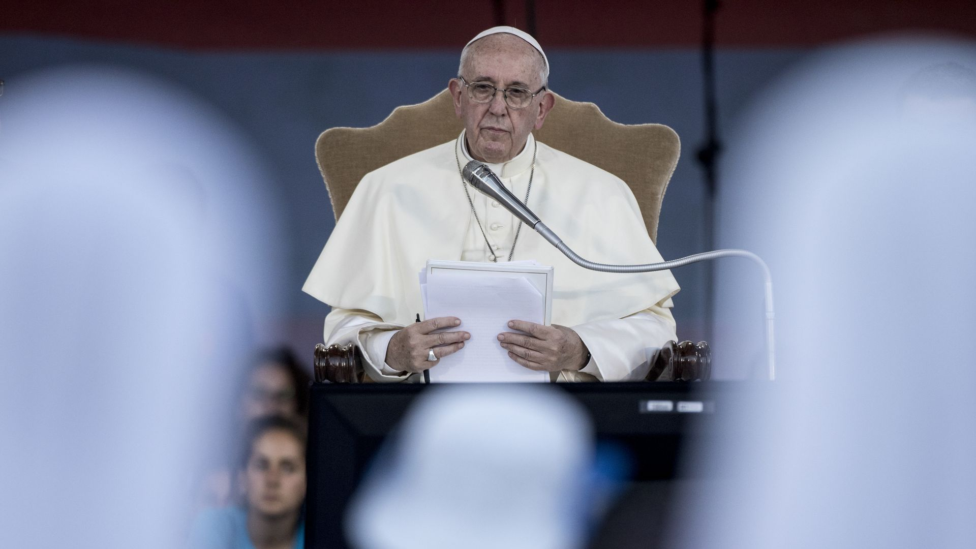 Pope Francis sitting at a mic but not talking