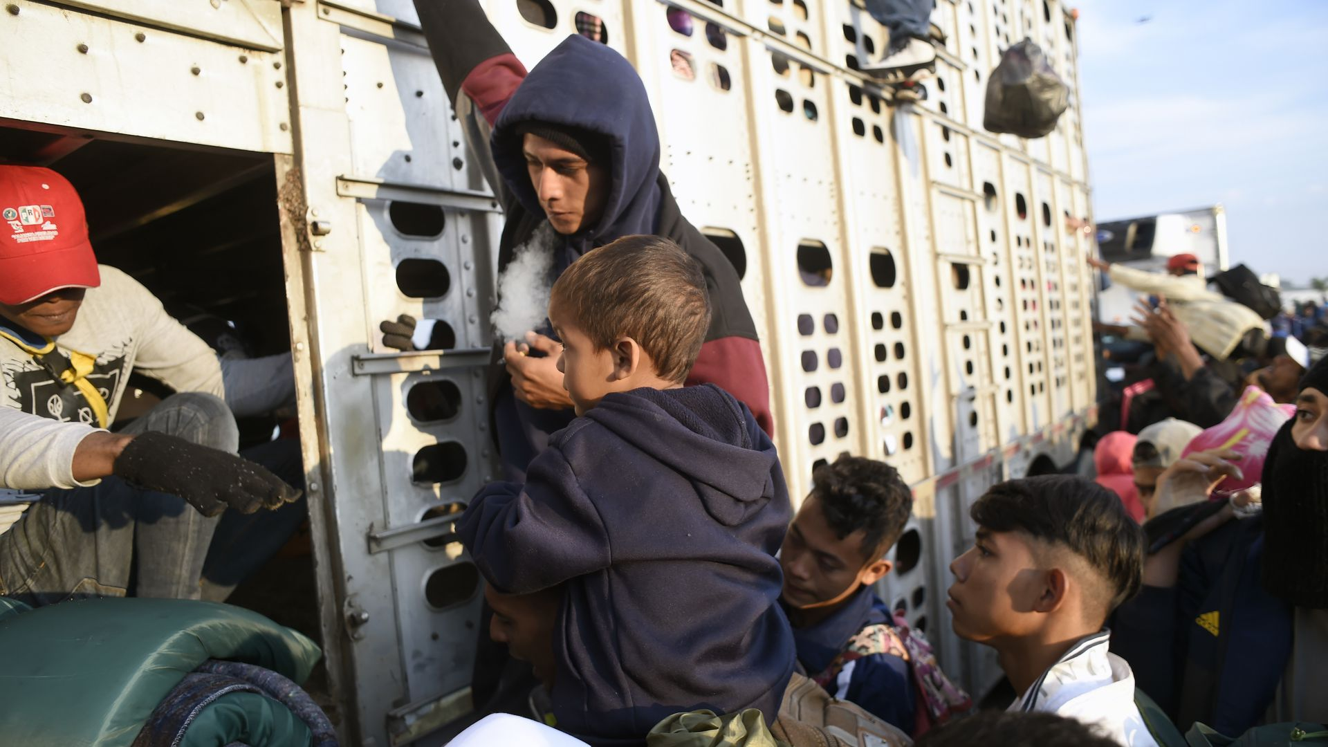 A crowd of Central American migrants, including some children, crowd around a boxcar where they are trying to get on to travel toward the U.S.