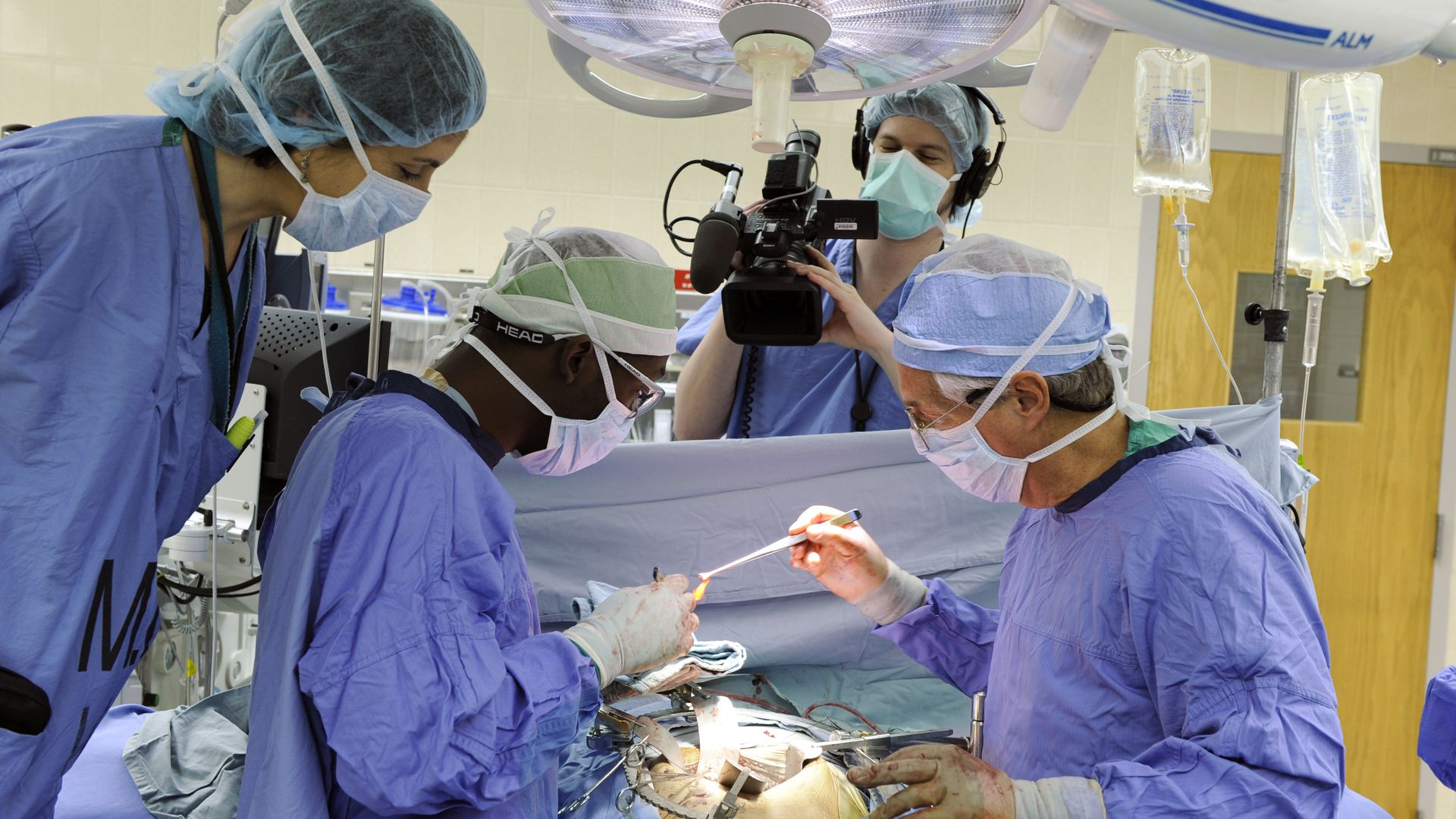 A camerawoman in scrubs films a surgery on ABC's Boston Med