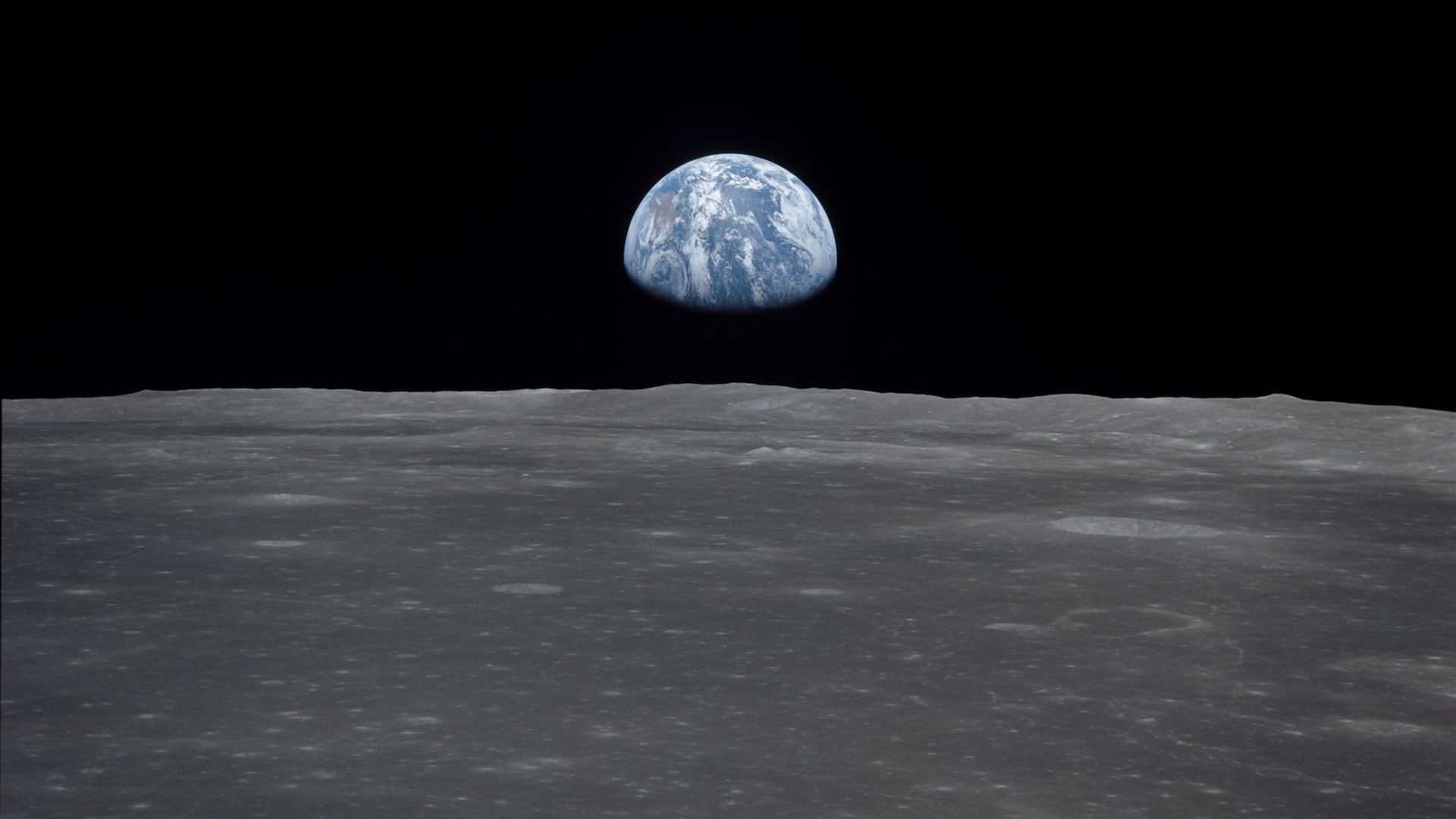 Earth rising above the moon.