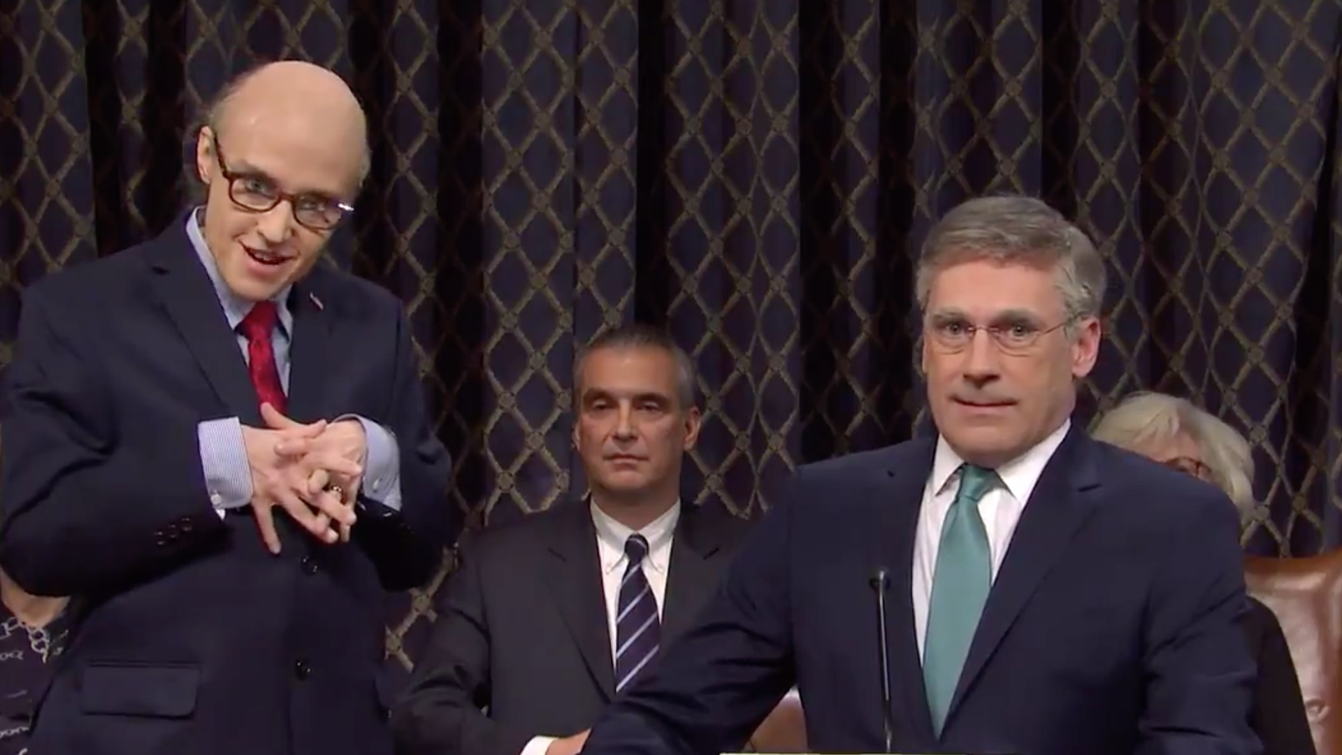 A screenshot of Jon Hamm as Bill Taylor, the top U.S. diplomat in Ukraine, and Kate McKinnon as President Trump's personal lawyer Rudy Giuliani.