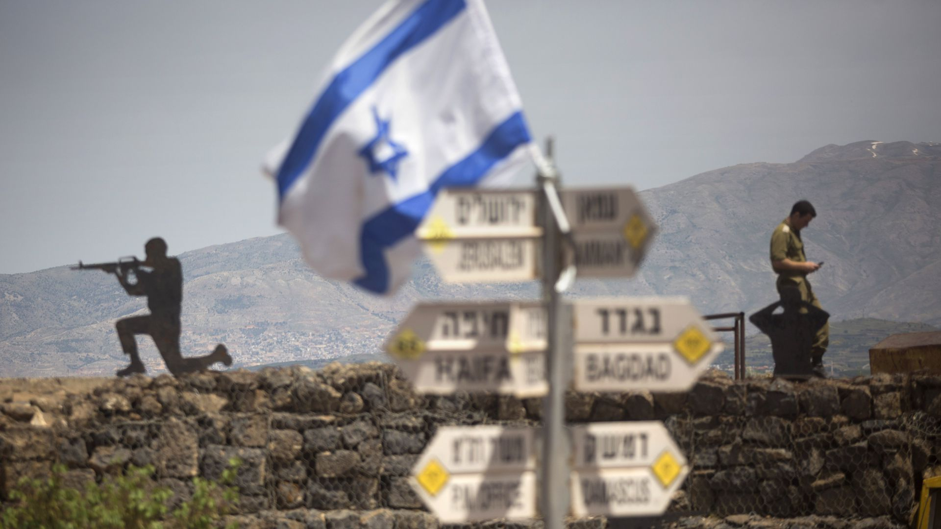 Israeli soldier is seen next to a signs pointing out distance to different cities on Mount Bental next to the Syrian border on May 10, 2018 in the Israeli-annexed Golan Heights.