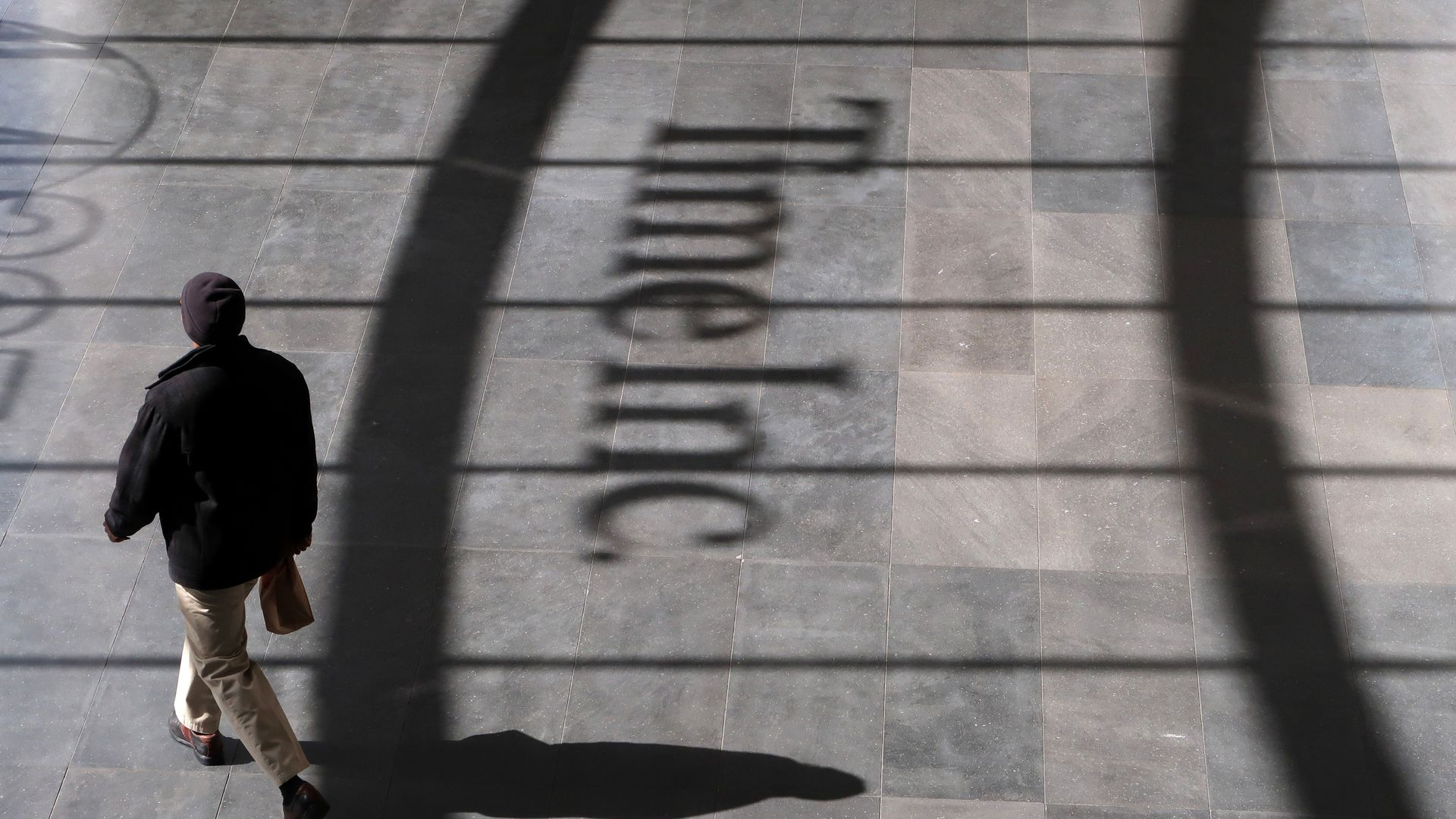 Man walking past shadow of Time Inc. headquarters in lower Manhattan.