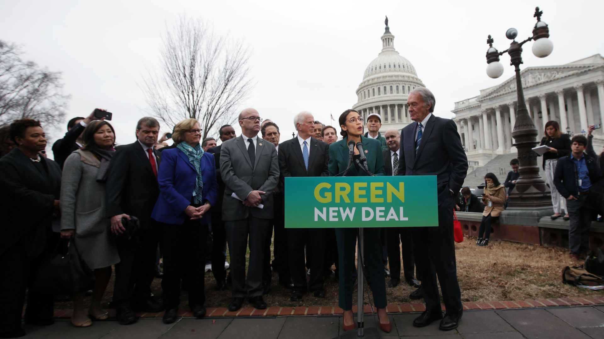 "In this image, Alexandria Ocasio-Cortez stands alongside other Democrats outside the Capitol building on a sunny day in Washington. They hold a banner that says ""Green New Deal."""