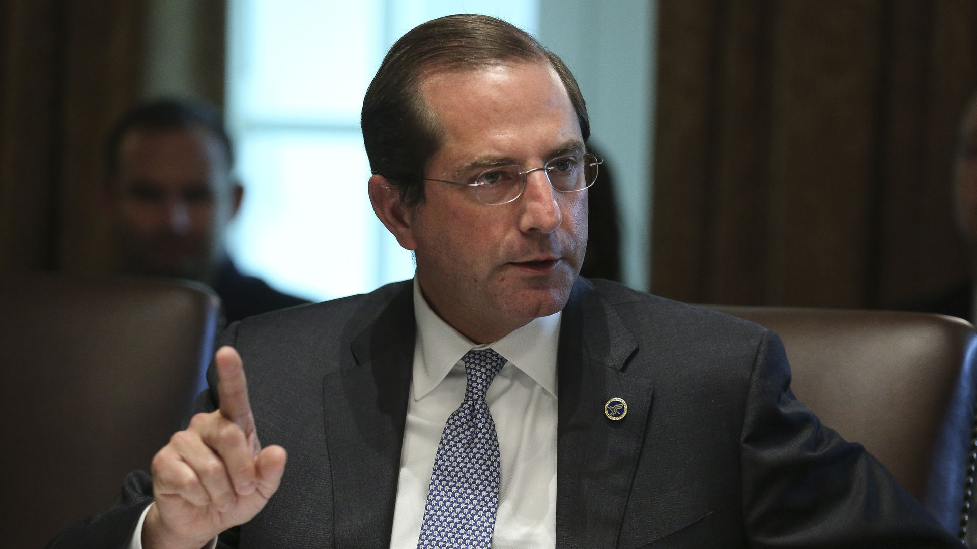 HHS Secretary Alex Azar sits and talks in a brown leather chair, pointing his index finger at the ceiling.