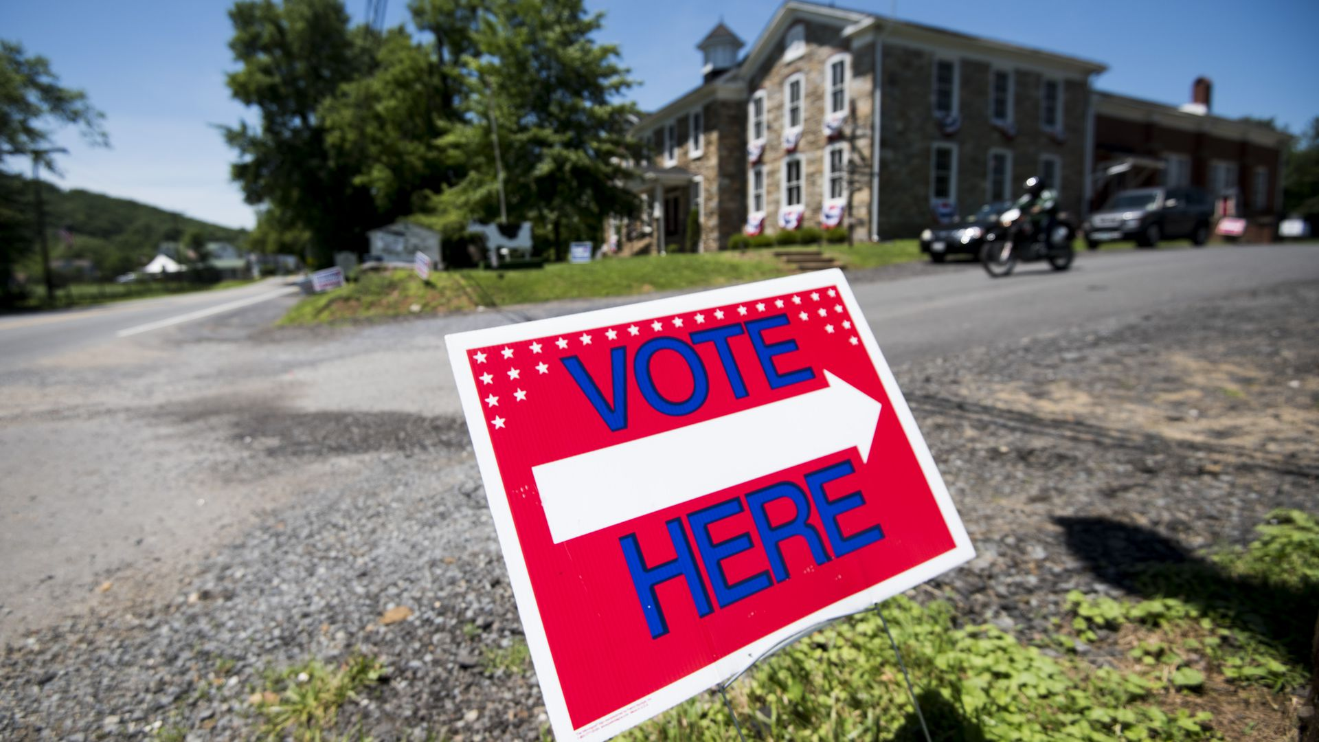 Vote here sign on a lawn pointing to a large building