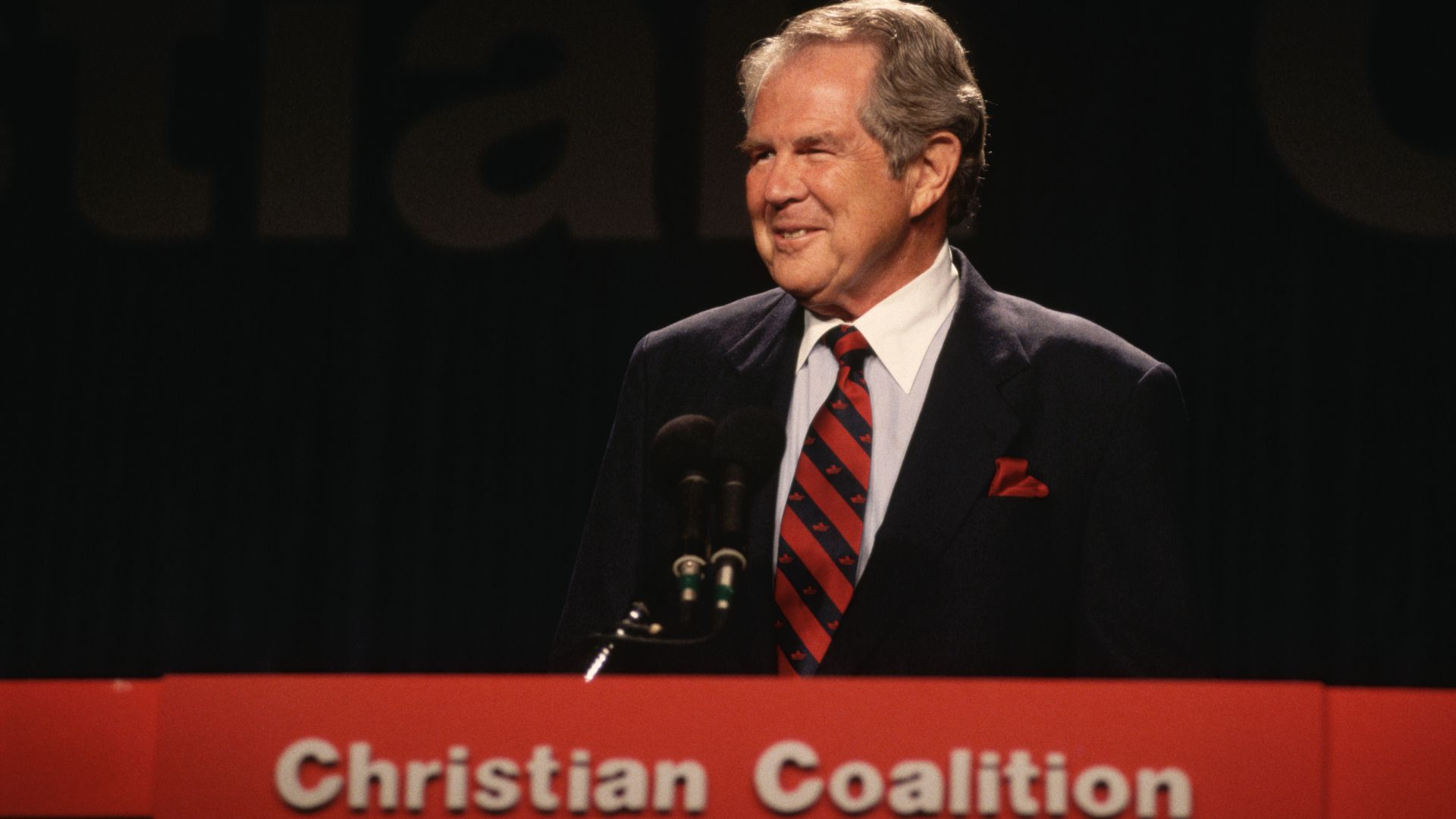 "An old photograph of Pat Robertson speaking at a podium with a sign that says ""Christian Coalition"" underneath it"