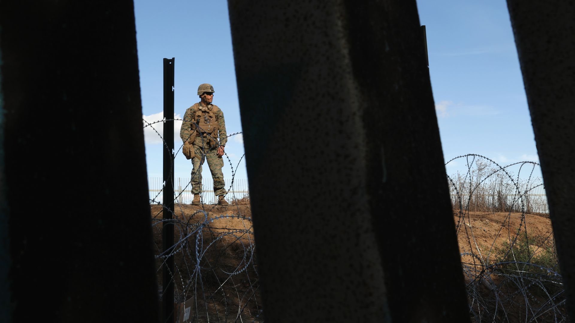 In this image, a Marine is seen in the distance between two fence poles that are close up against the camera. The clear sky is behind the Marine, who is in full uniform.