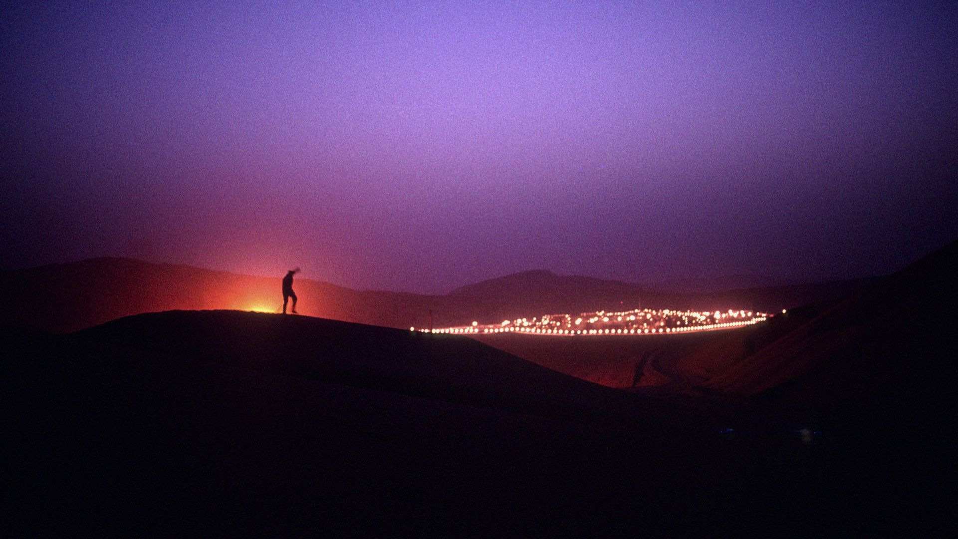 A man stands on a sand dune at night outside of a Saudi Aramco oil field complex
