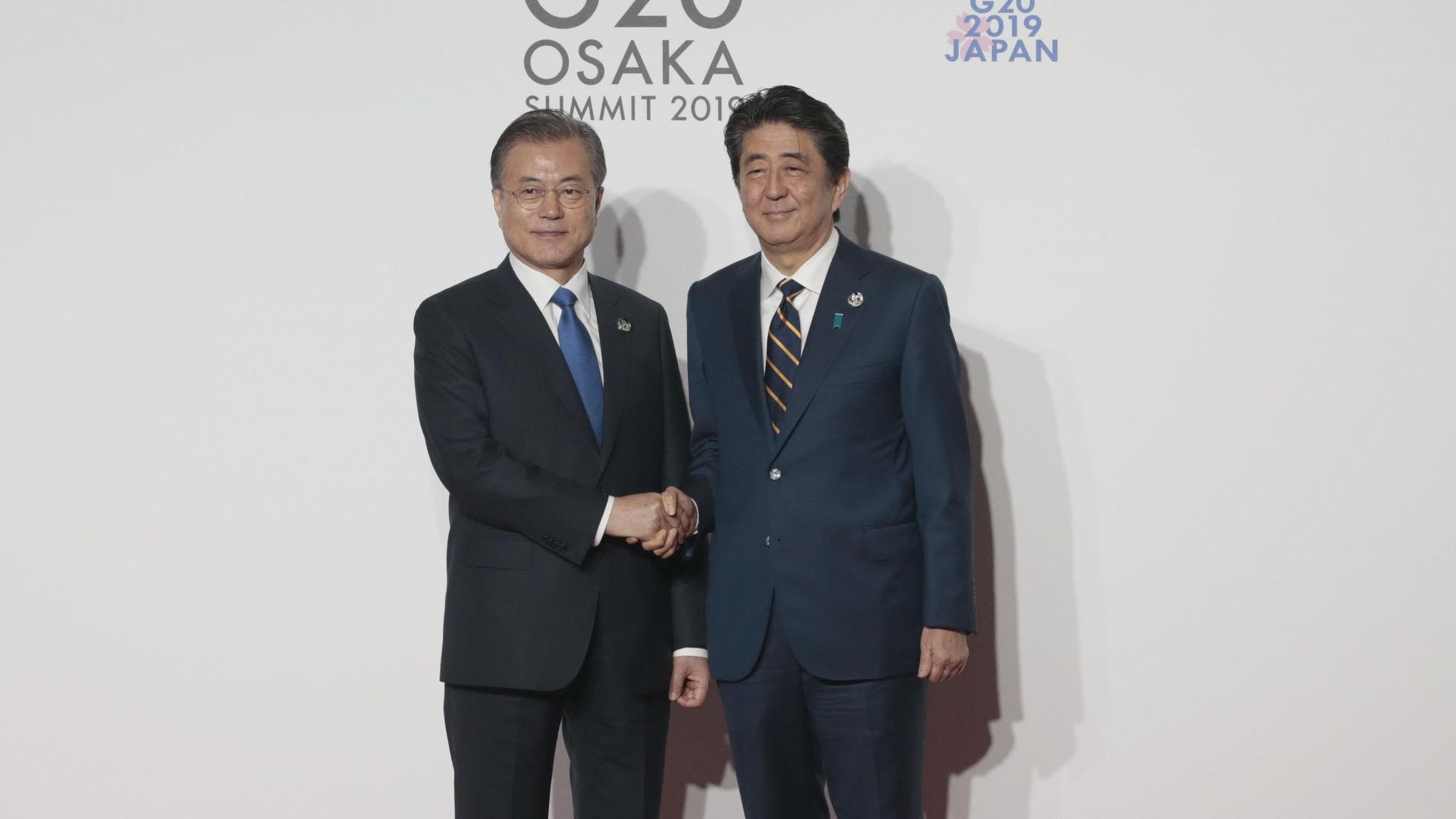 South Korea President Moon Jae-in is welcomed by Japanese Prime Minister Shinzo Abe on the first day of the G20 summit in Osaka, Japan