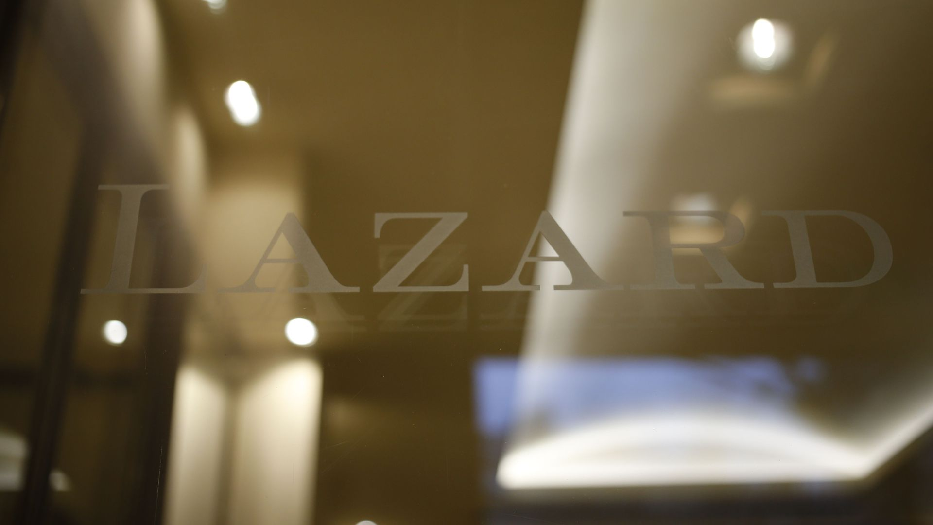 The logo of Lazard on a glass door.