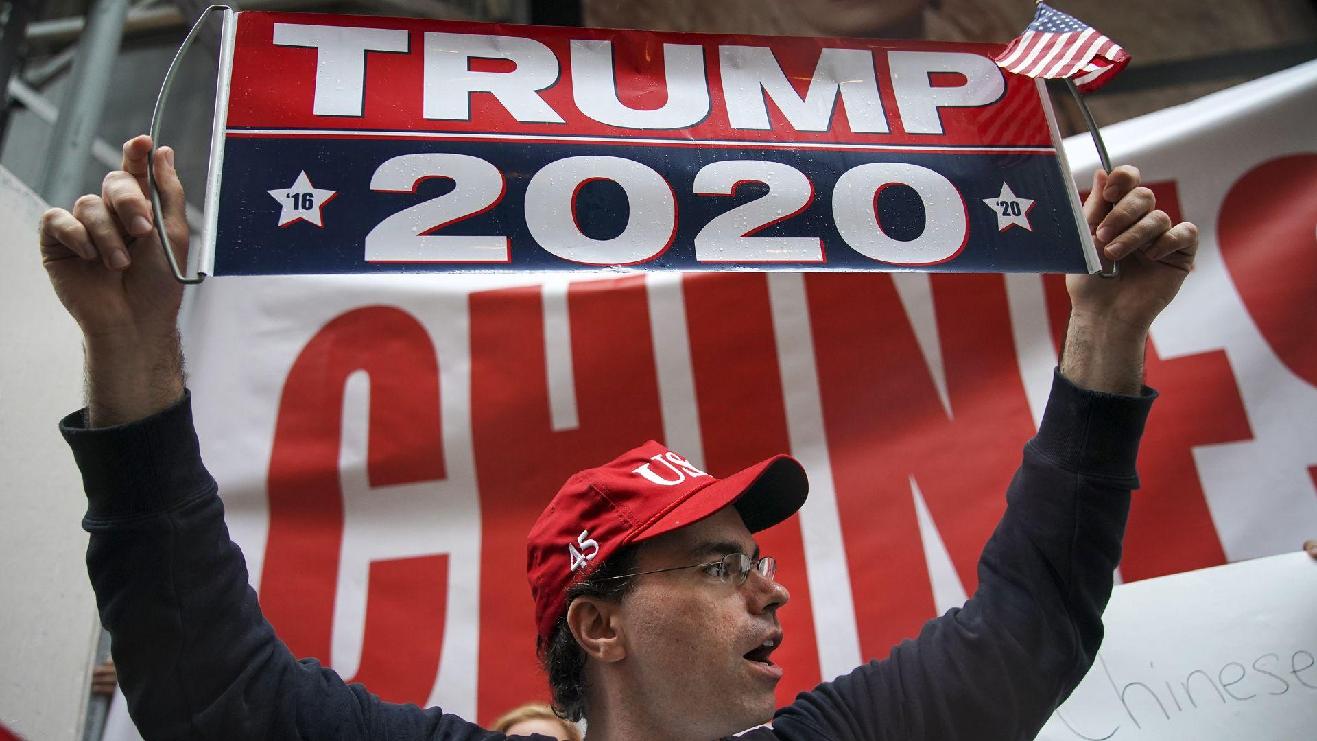 "In this image, a man holds up a banner that reads ""Trump 2020"""