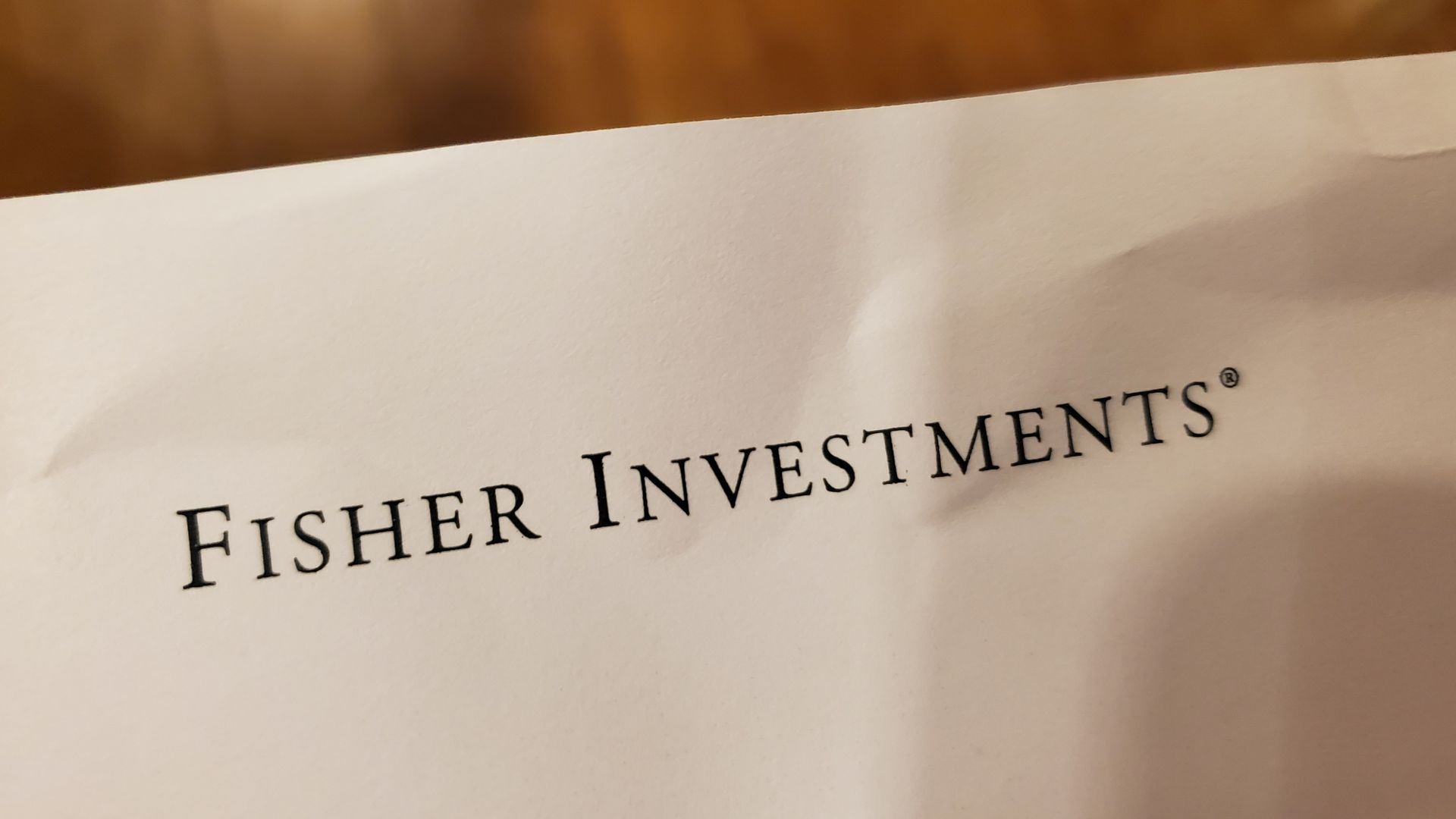 Close-up of logo for financial management company Fisher Investments on paper on light wooden background.