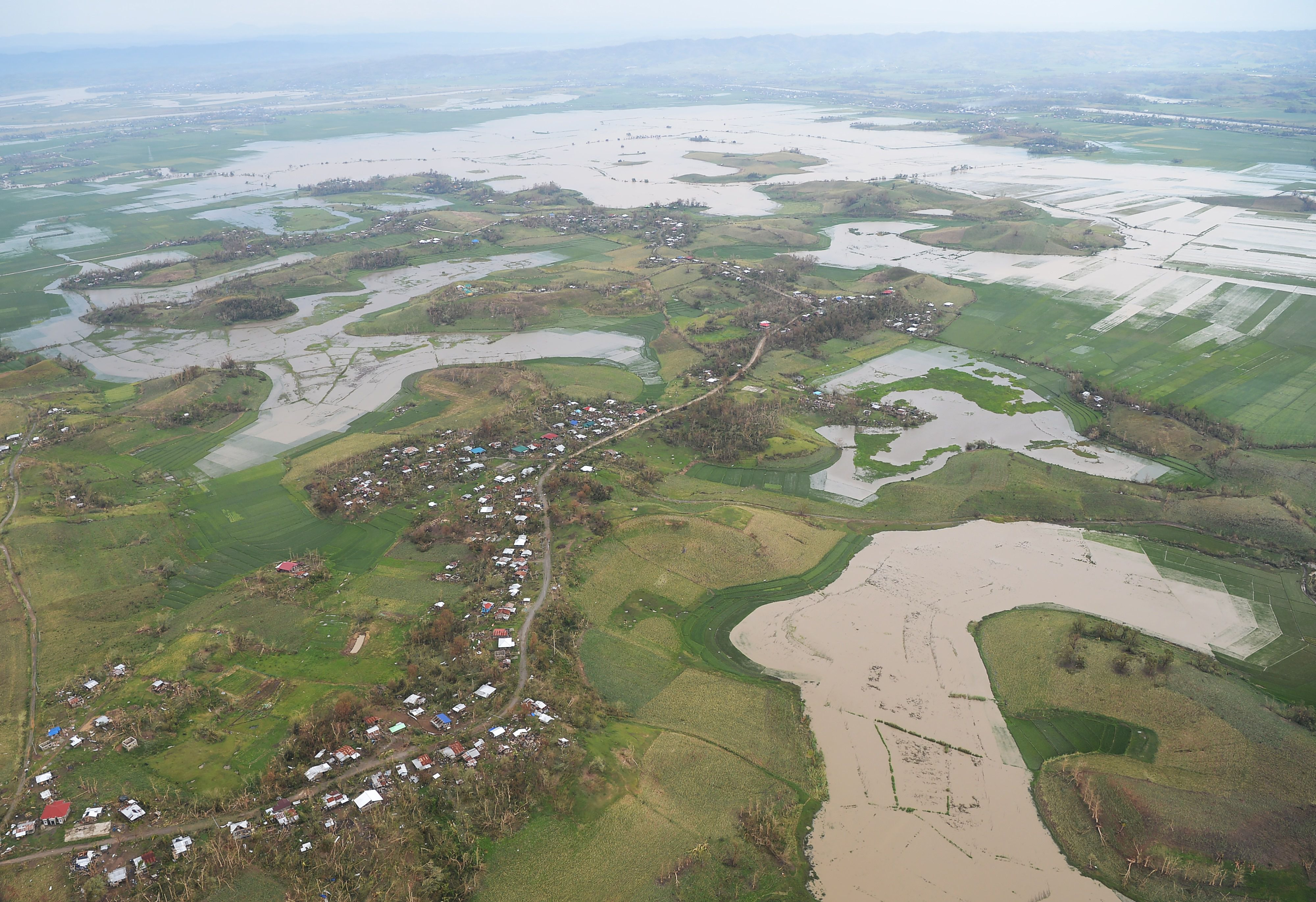 An aerial photo shows devastated homes and rice and corn fields inundated by floods.