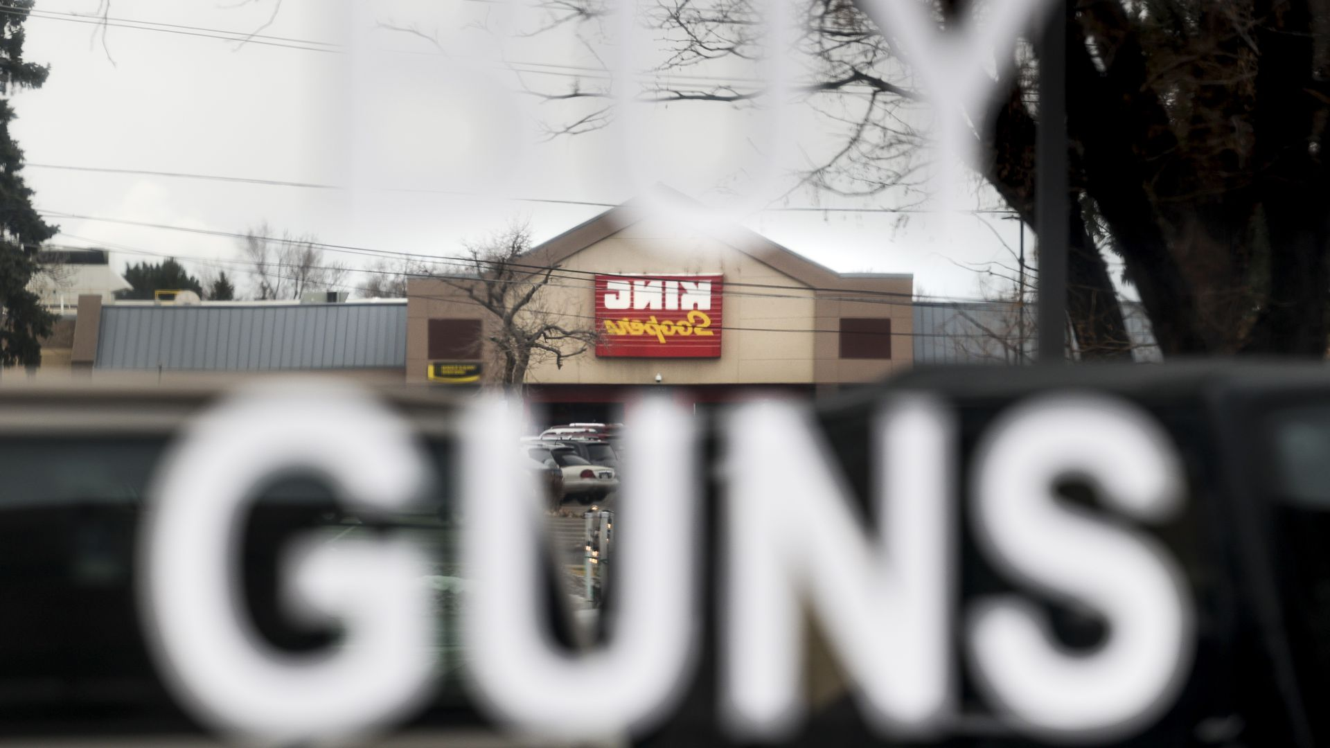 A King Soopers grocery store, not connected to the Boulder shooting, is reflected in the window of the Eagles Nest Armory in Arvada.
