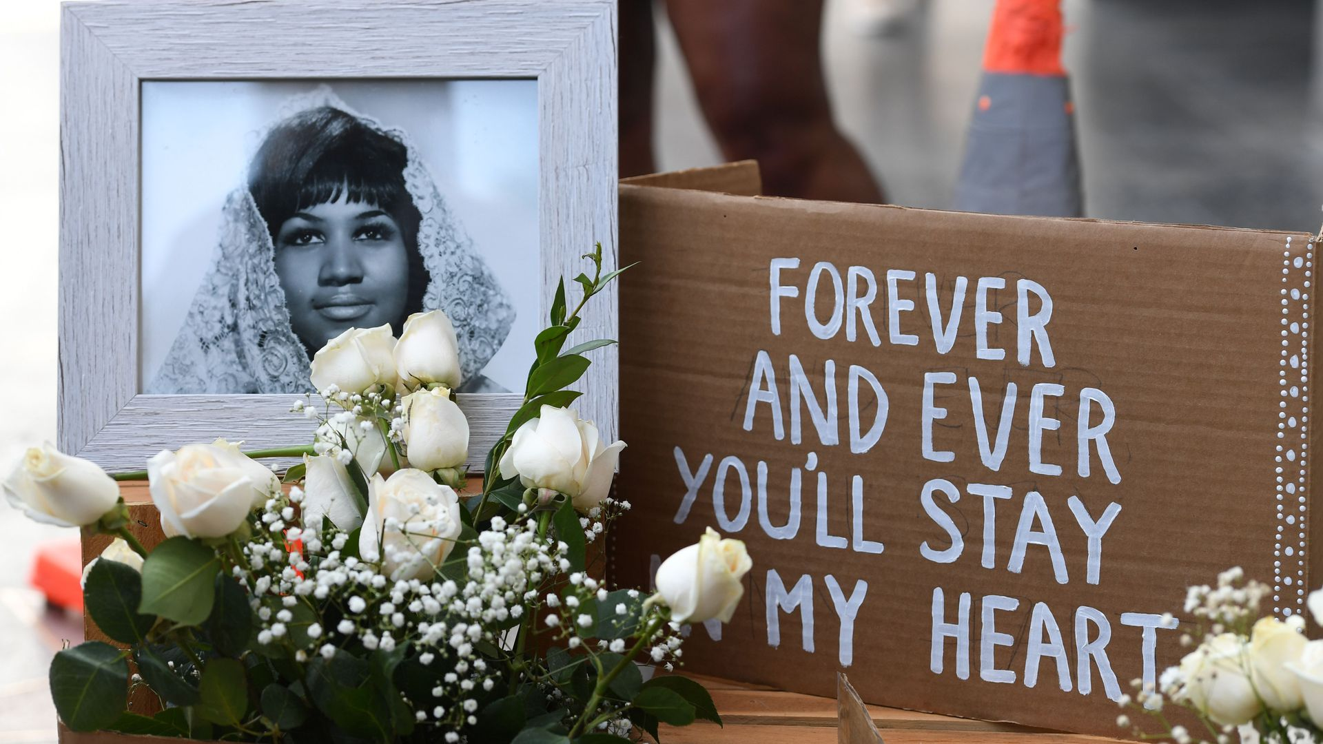 "A photo of Aretha Franklin with flowers and a sign reading, ""Forever you'll stay in my heart"""