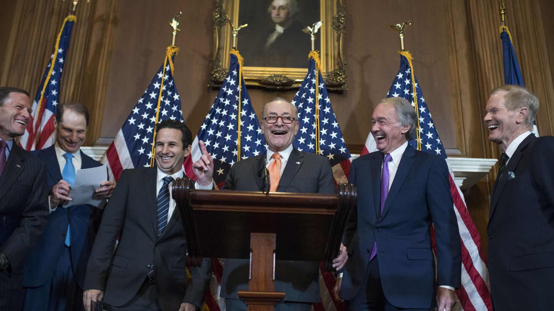 Sen. Chuck Schumer at a podium, surrounded by other Senate Democrats
