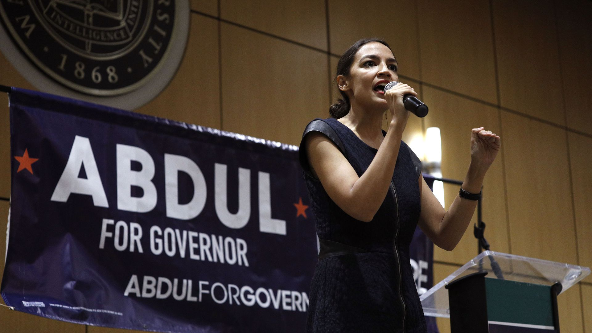 Alexandria Ocasio-Cortez on stage in front of an Abdul for Governor poster