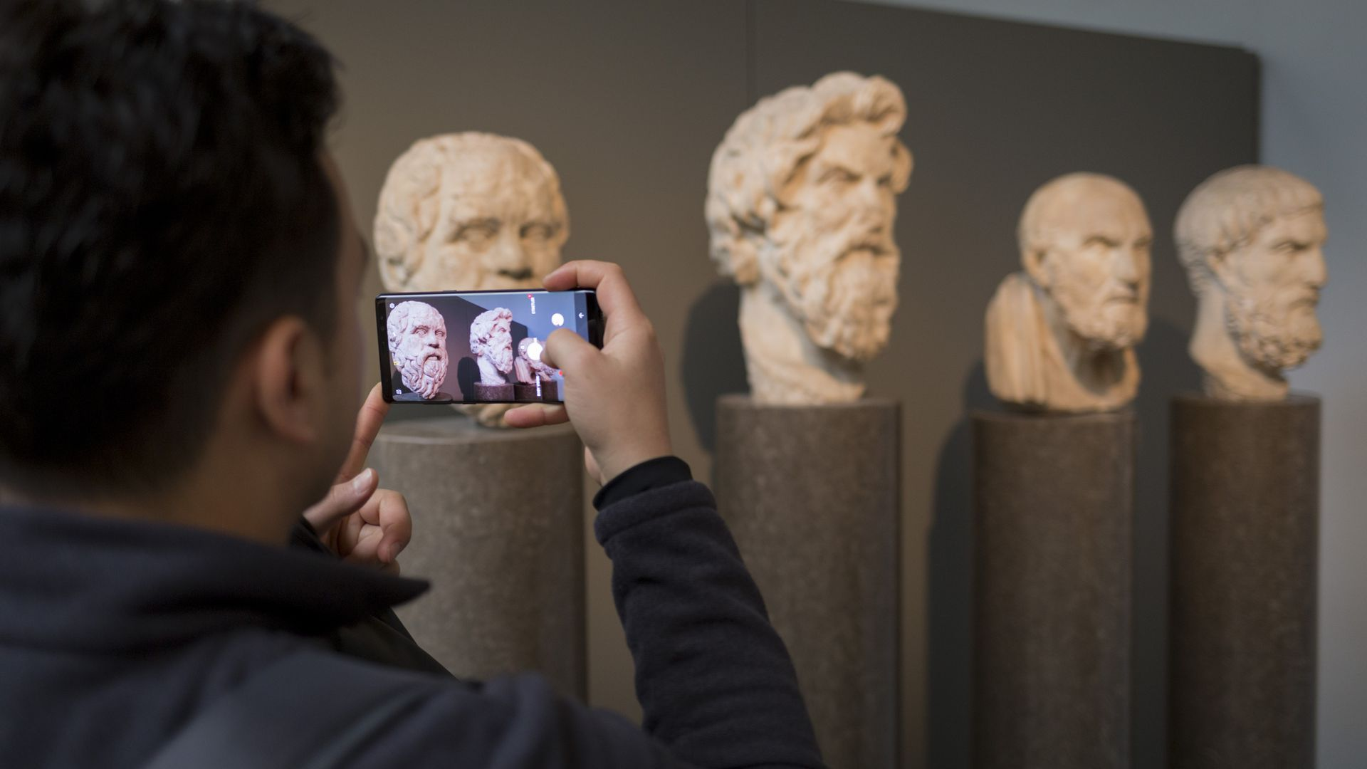 A visitor takes a picture of the heads of ancient Greek philosophers