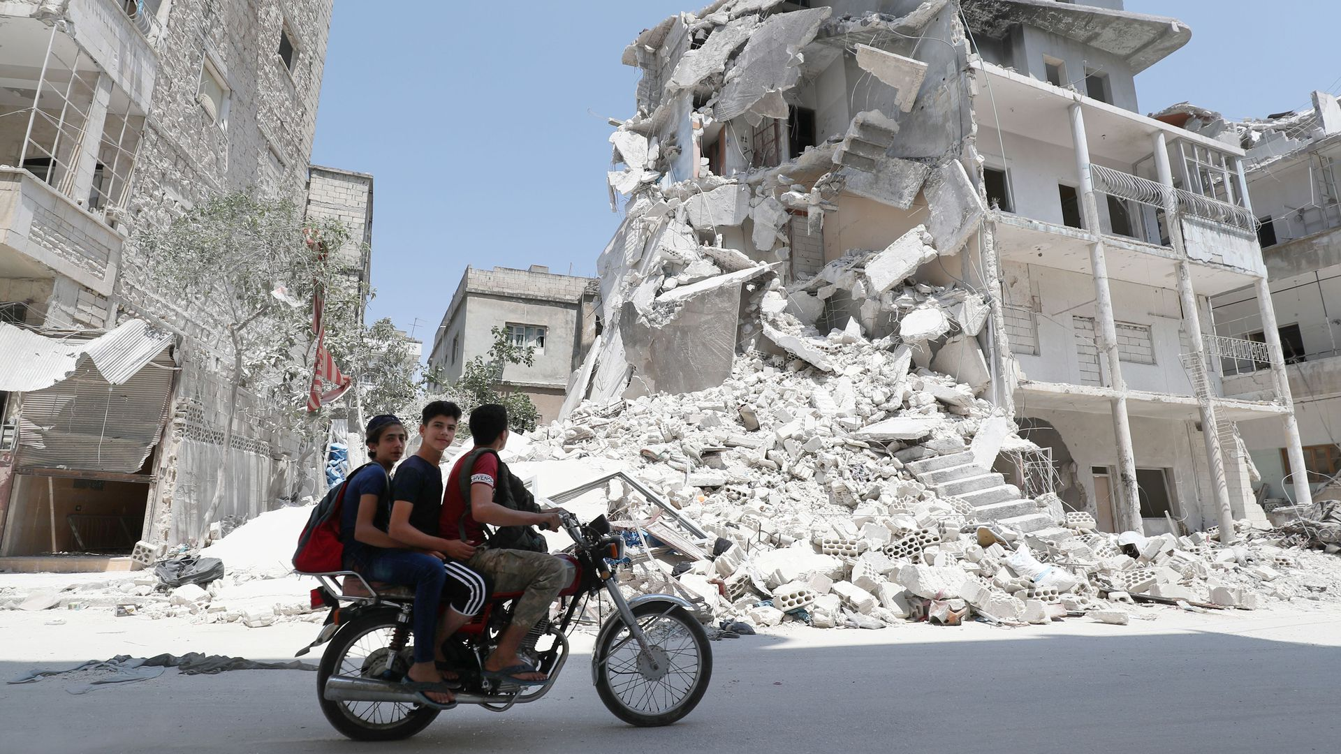 Men on a motorcycle ride by an airstrike-damaged building