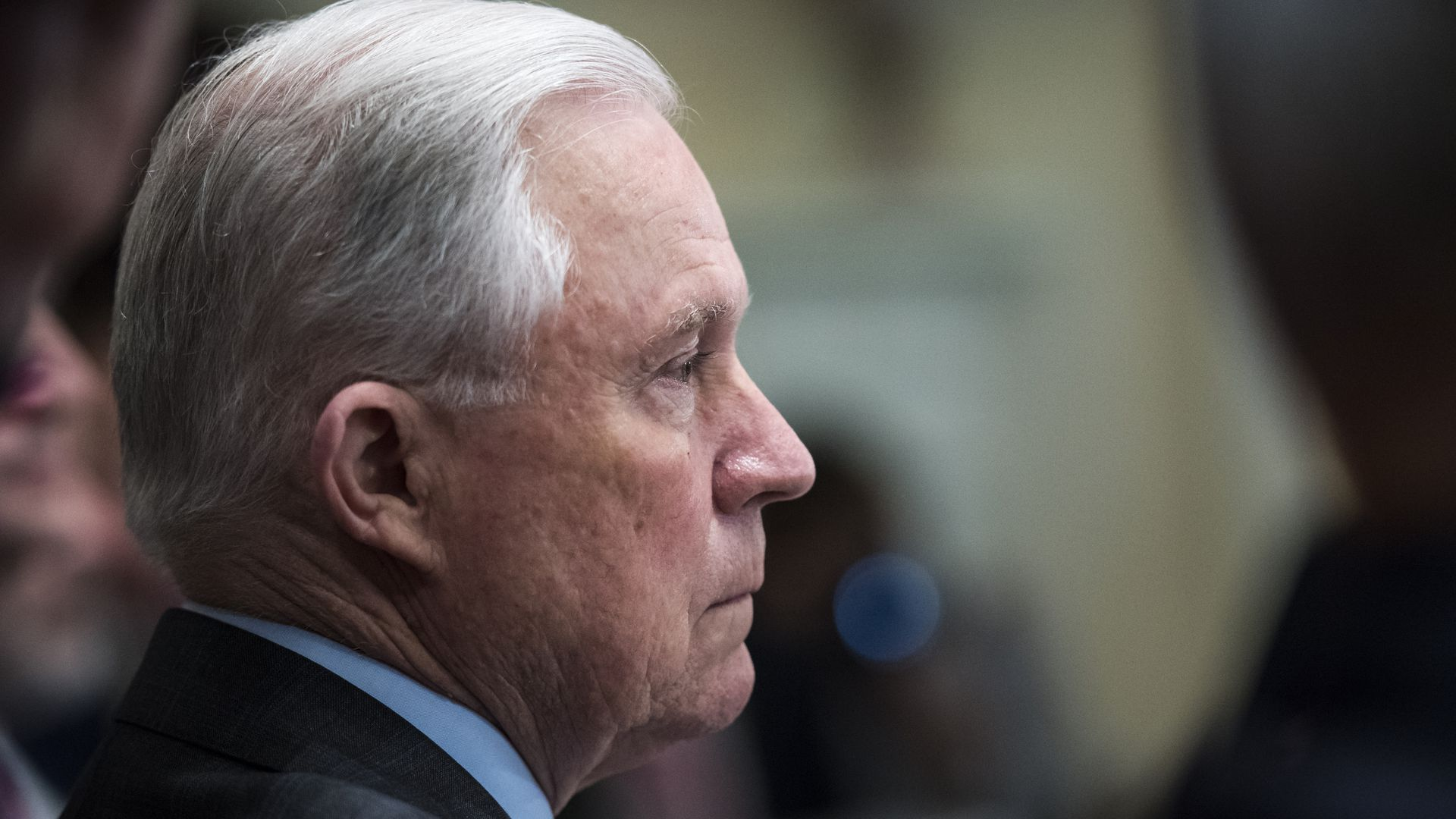 Jeff Sessions profile sitting at a table looking unhappy.