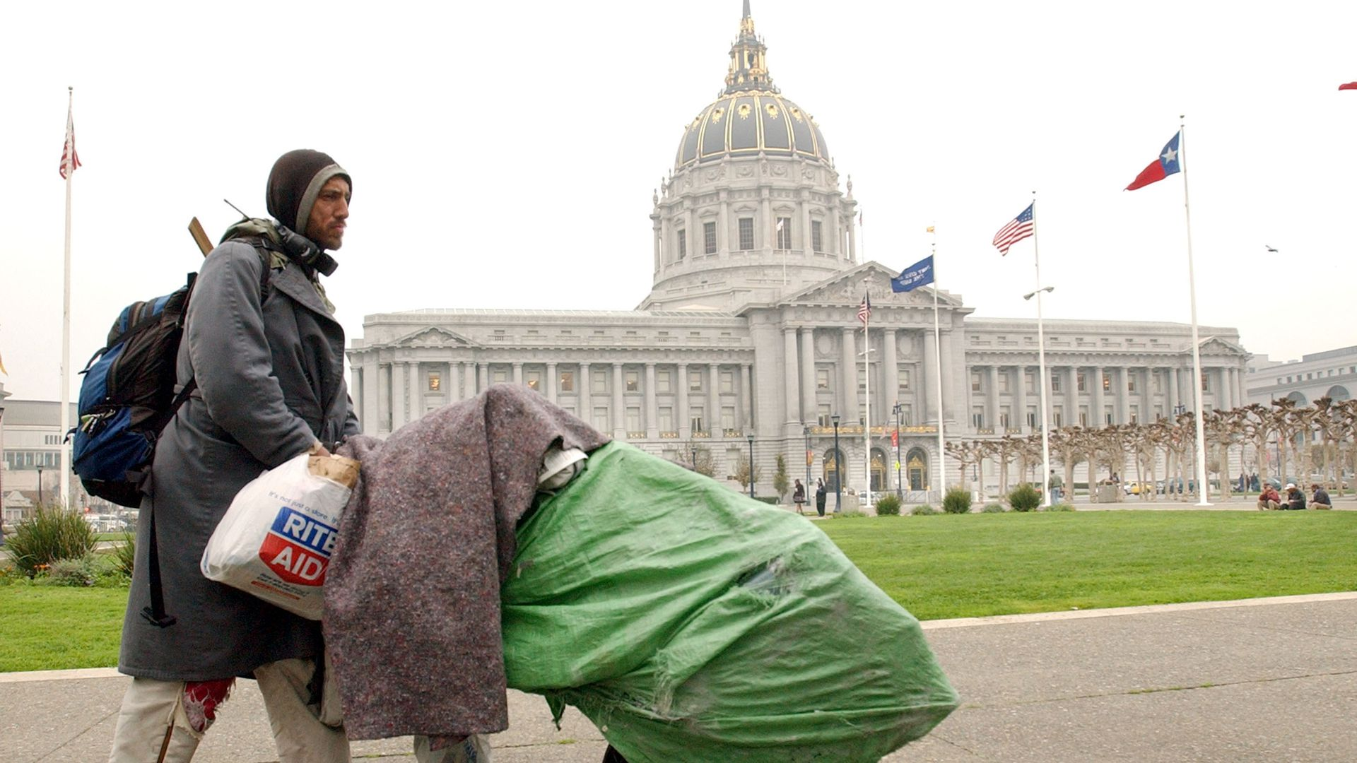 Homeless man pushes green rolly bag in front of San Francisco City Hall dome.
