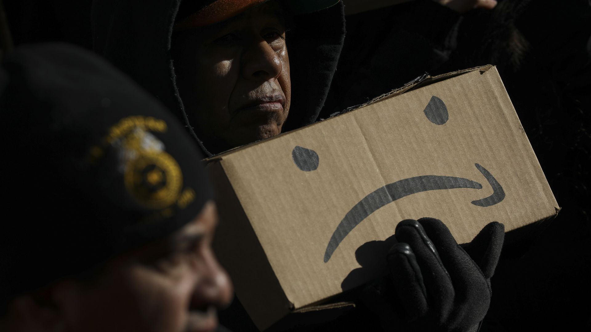 A man holds an upside-down Amazon logo with two eyes, made to look like a sad face