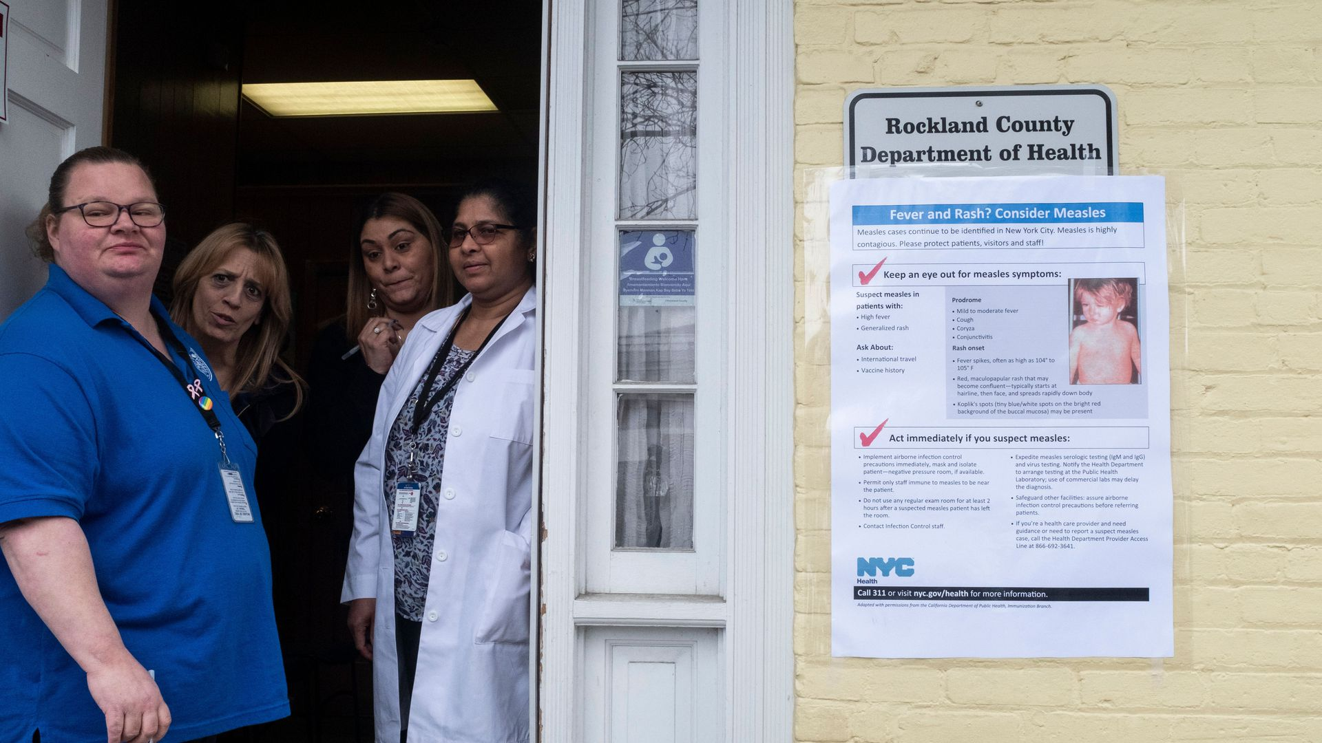 Photo of nurses at a clinic in Rockland County, NY, peering outside the door next to a measles information sign