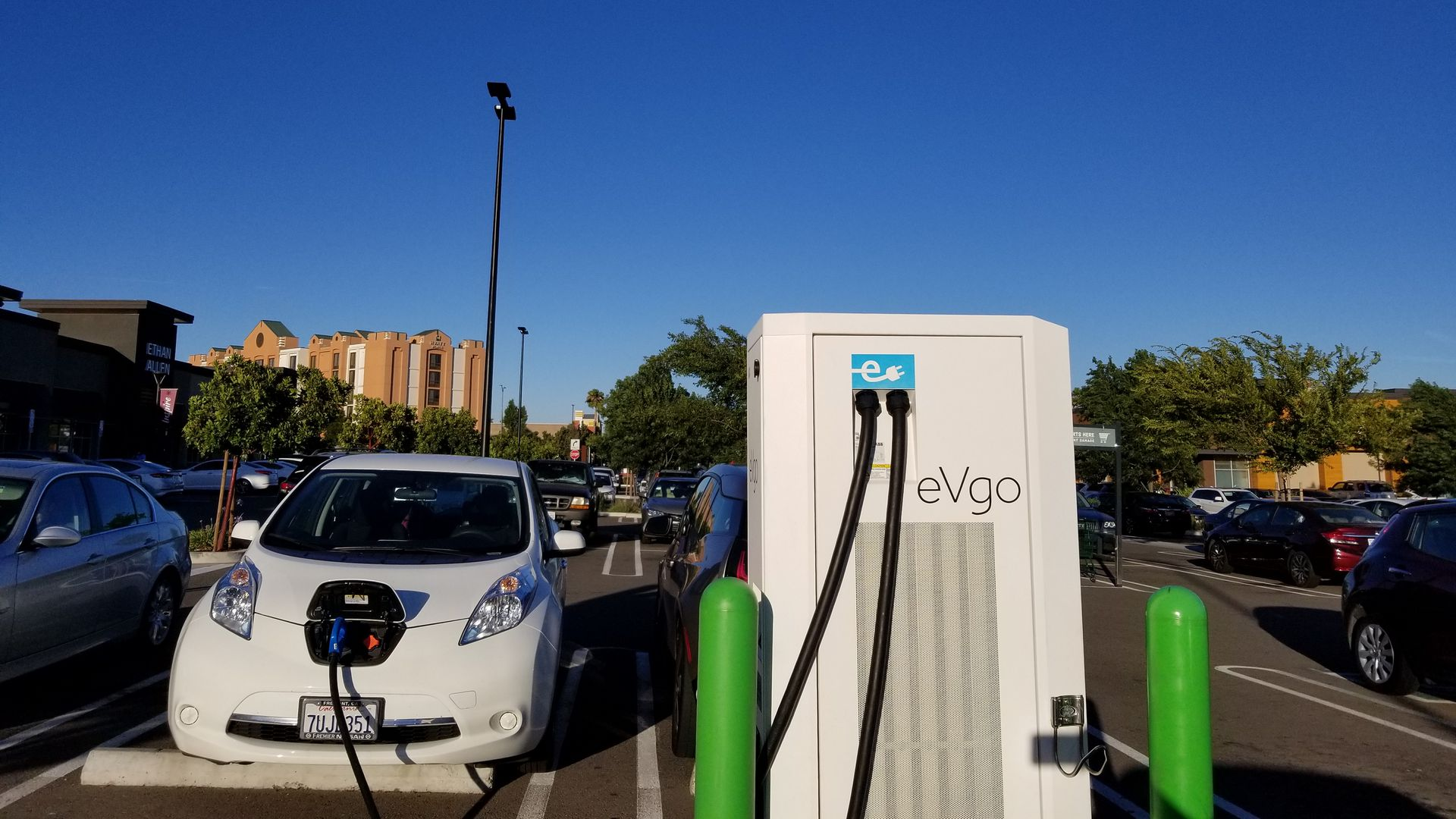 In this image, an electric car is plugged into a charger in a sunny parking lot