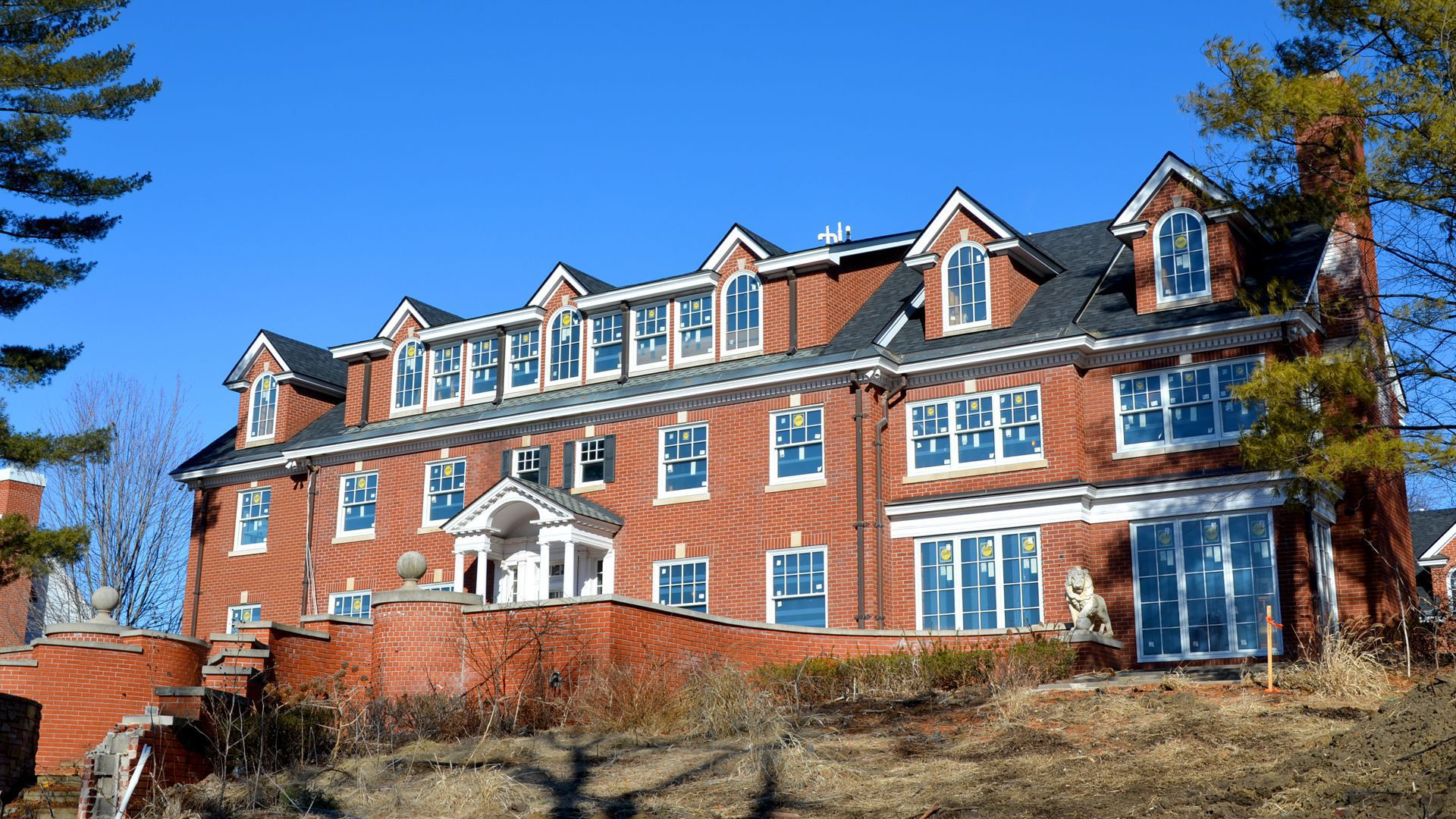 Brick house with four garret windows at the top and two floors visible behind a brick wall.