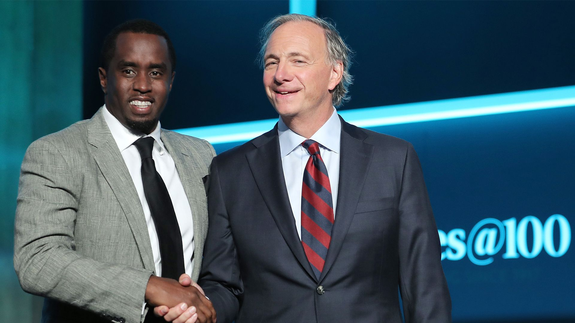 In this image, Dalio and Diddy stand together and shake hands while wearing suits