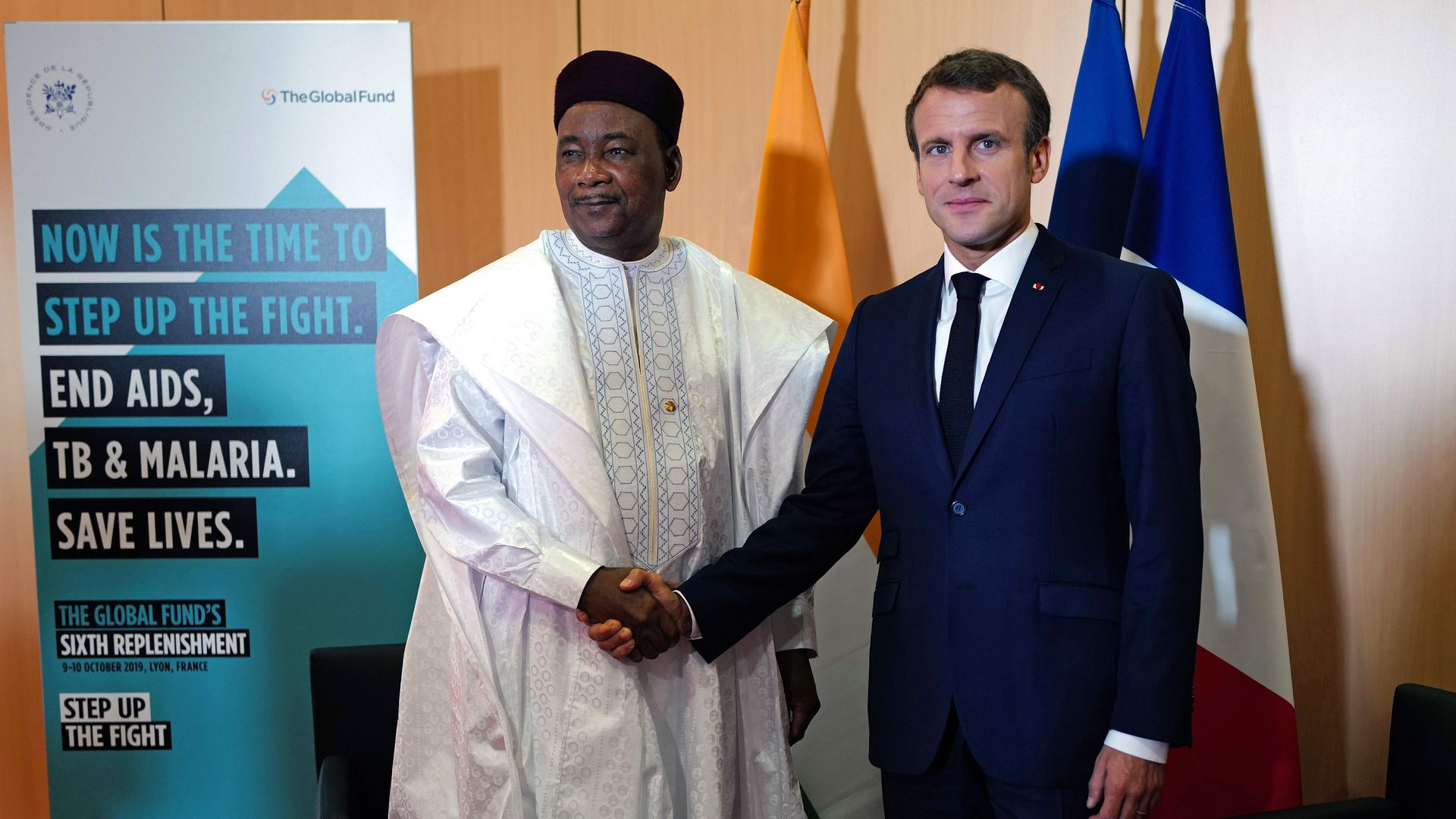 Emmanel Macron and Mahamadou Issoufou shake hands in front of flags and a Global Fund sign