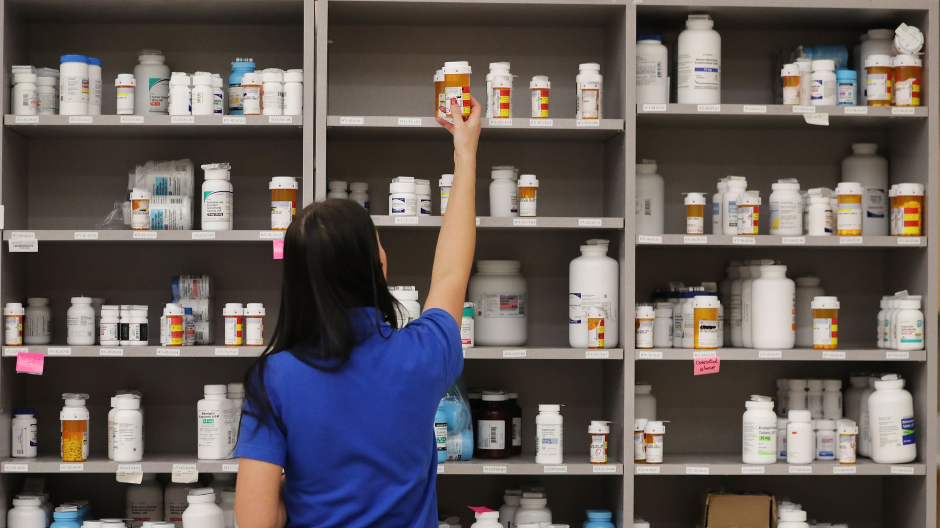 A pharmacist reaches for a bottle among shelves of prescription drugs