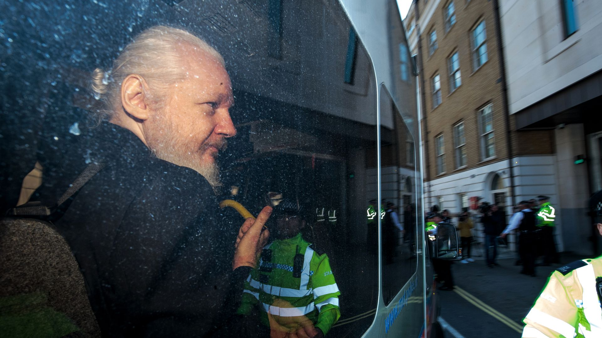 In this image, Julian Assange looks out a vehicle window.