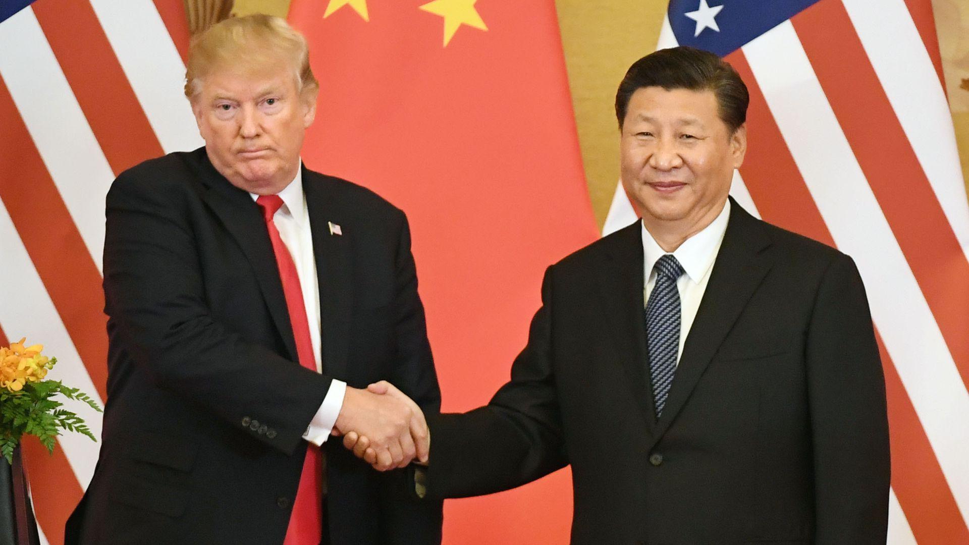 Donald Trump shakes Xi Jinping's hand.
