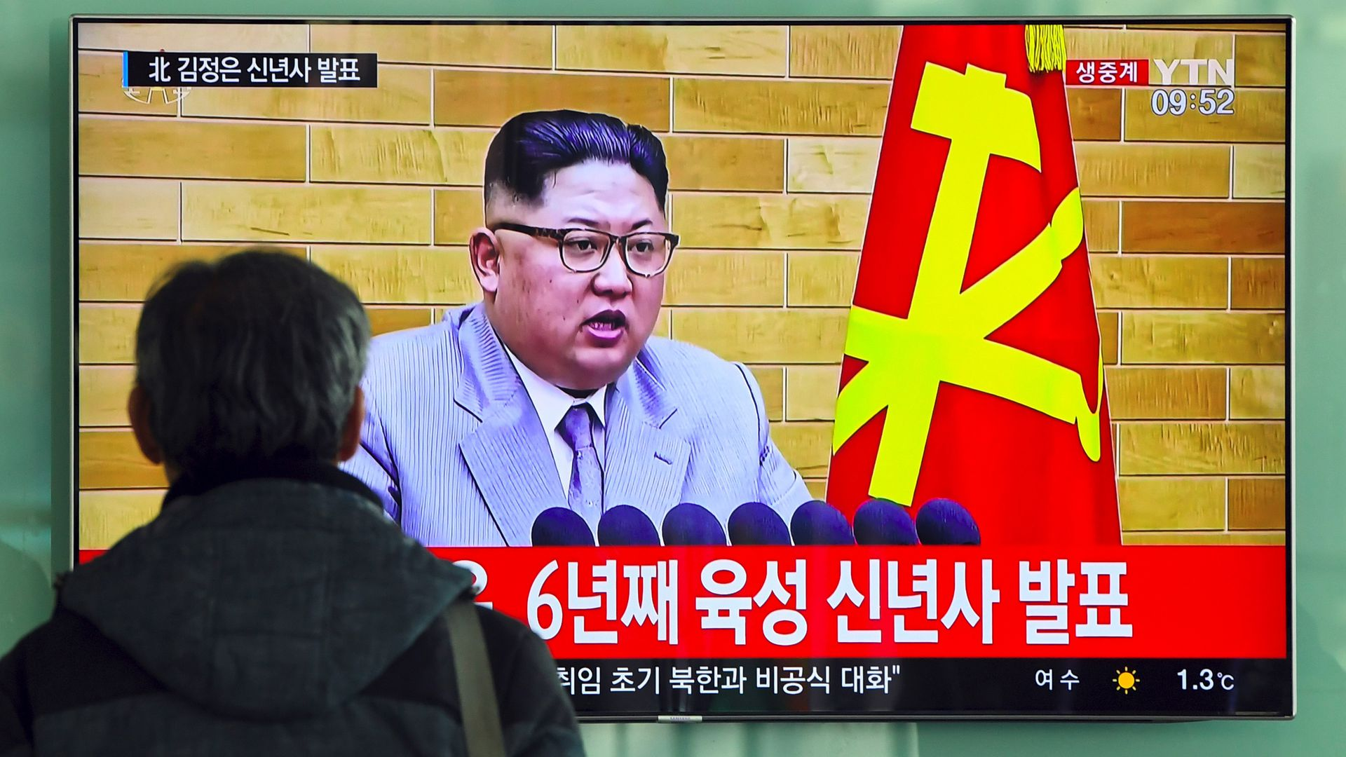 A man watches a television news broadcast showing Kim Jong-Un.